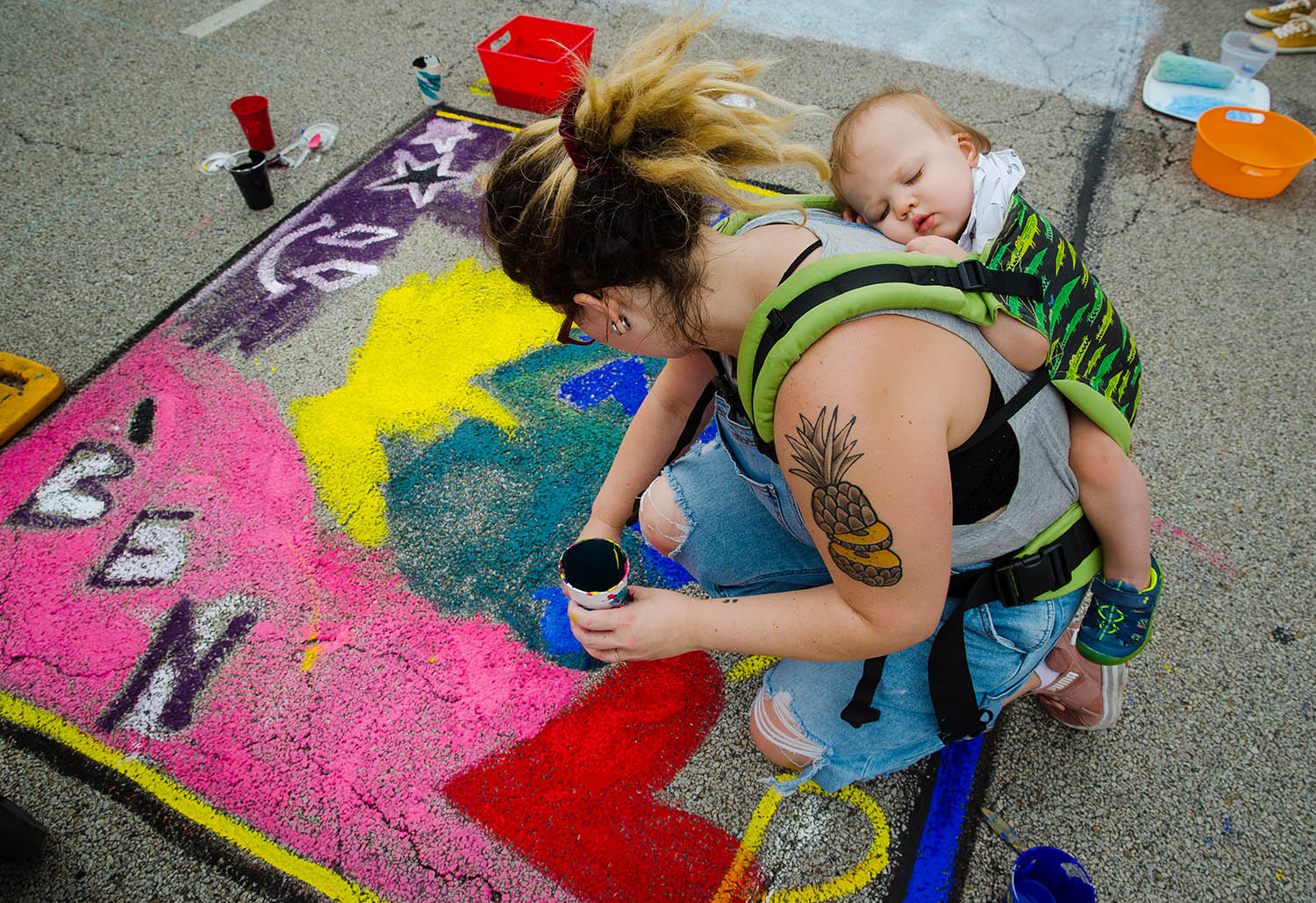 Rachel Morrison's one-year-old son Benjamin sleeps while nestled in a carrier on her back during the Springfield Art Association's 2019 Paint the Street event in downtown Springfield, Ill., Saturday, June 22, 2019. Morrison said painting was much harder while carrying her 20-pound son. [Ted Schurter/The State Journal-Register]