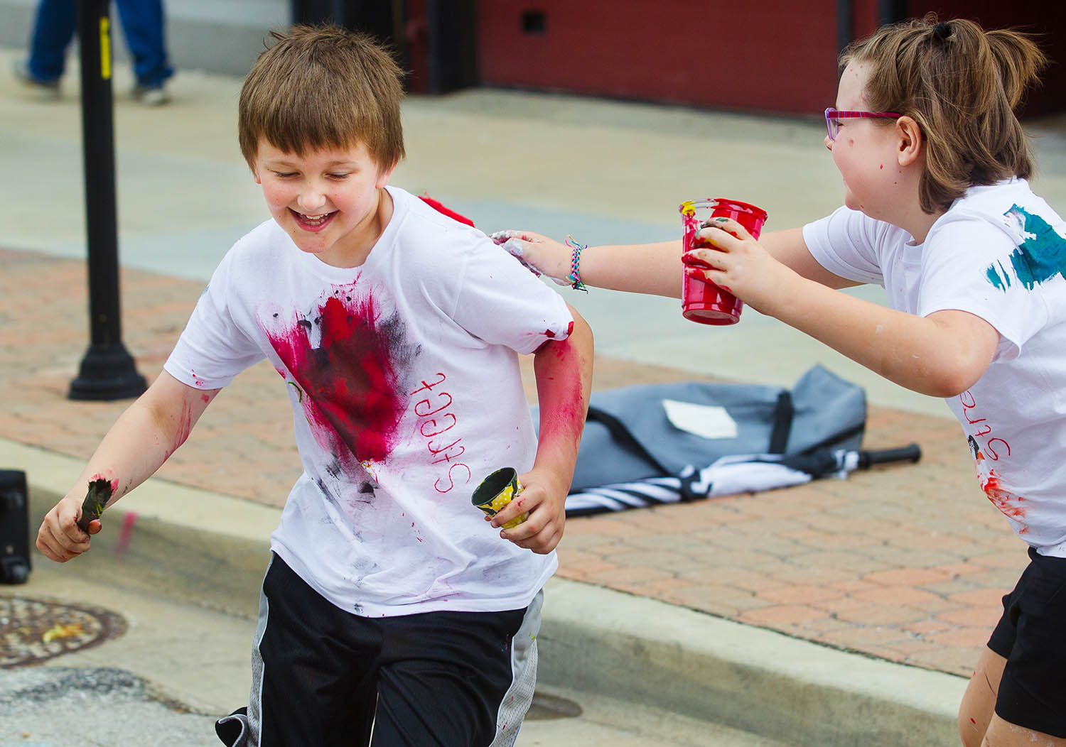 Liam Steinkruger runs from Reagan Burlison as she tries to swipe him with her red paint brush during the Springfield Art Association's 2019 Paint the Street event in downtown Springfield, Ill., Saturday, June 22, 2019. [Ted Schurter/The State Journal-Register]