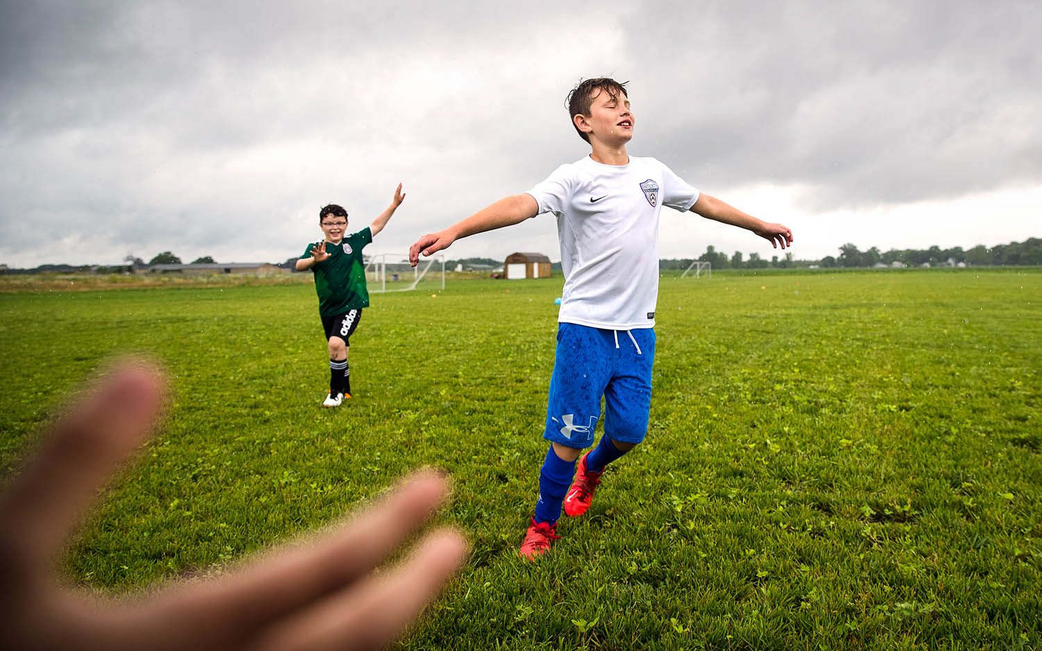 Oliver Buss, left, and Andrew Drennan dance around in the rain during a water break at the TetraBrazil Camp at Integrity Soccer Fields at Calvary Church in Springfield, Monday, June 24, 2019. Camp organizers said the training, which continues through Friday, includes warming up to samba music and learning some Portuguese phrases, emphasizes traditional Brazilian technical practices with the flair, passion, and creativity of South American soccer. [Ted Schurter/The State Journal-Register]