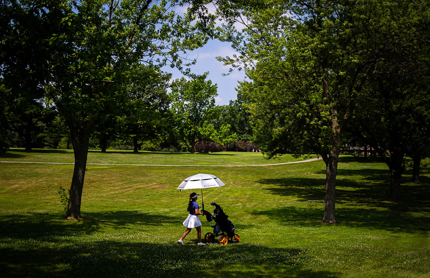 Karlie Schnepp travels with her own shade as she makes here way towards the green on the No. 9 hole on the opening day Drysdale Golf Tournament at Lincoln Greens Golf Course, Monday, July 8, 2019, in Springfield, Ill. [Justin L. Fowler/The State Journal-Register]