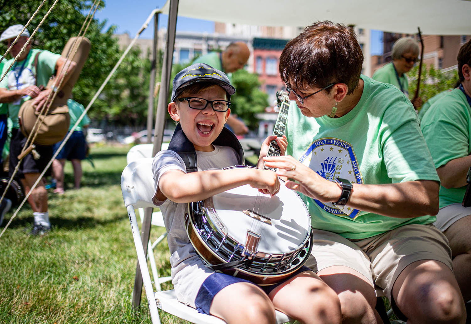 Henry Morton, 7, of Lakemoor, Ill., smiles as he hears and plays a note on a banjo for the first time as Nora Bardi, of Bloomington, Ill., shows him how to strum the strings before the the All Frets Flash Mob performs on the Old State Capitol, Friday, July 12, 2019, in Springfield, Ill. The All Frets Flash Mob are part of a group of banjo players that have congregated in Springfield for the All Frets Convention hosted by the Central Illinois Banjo Club at the Crowne Plaza. The convention, which is dedicated to music played on banjos, ukuleles, mandolins, guitars and other fretted instruments, concludes on Saturday with a concert at the Crowne Plaza starting at 7 p.m. [Justin L. Fowler/The State Journal-Register]