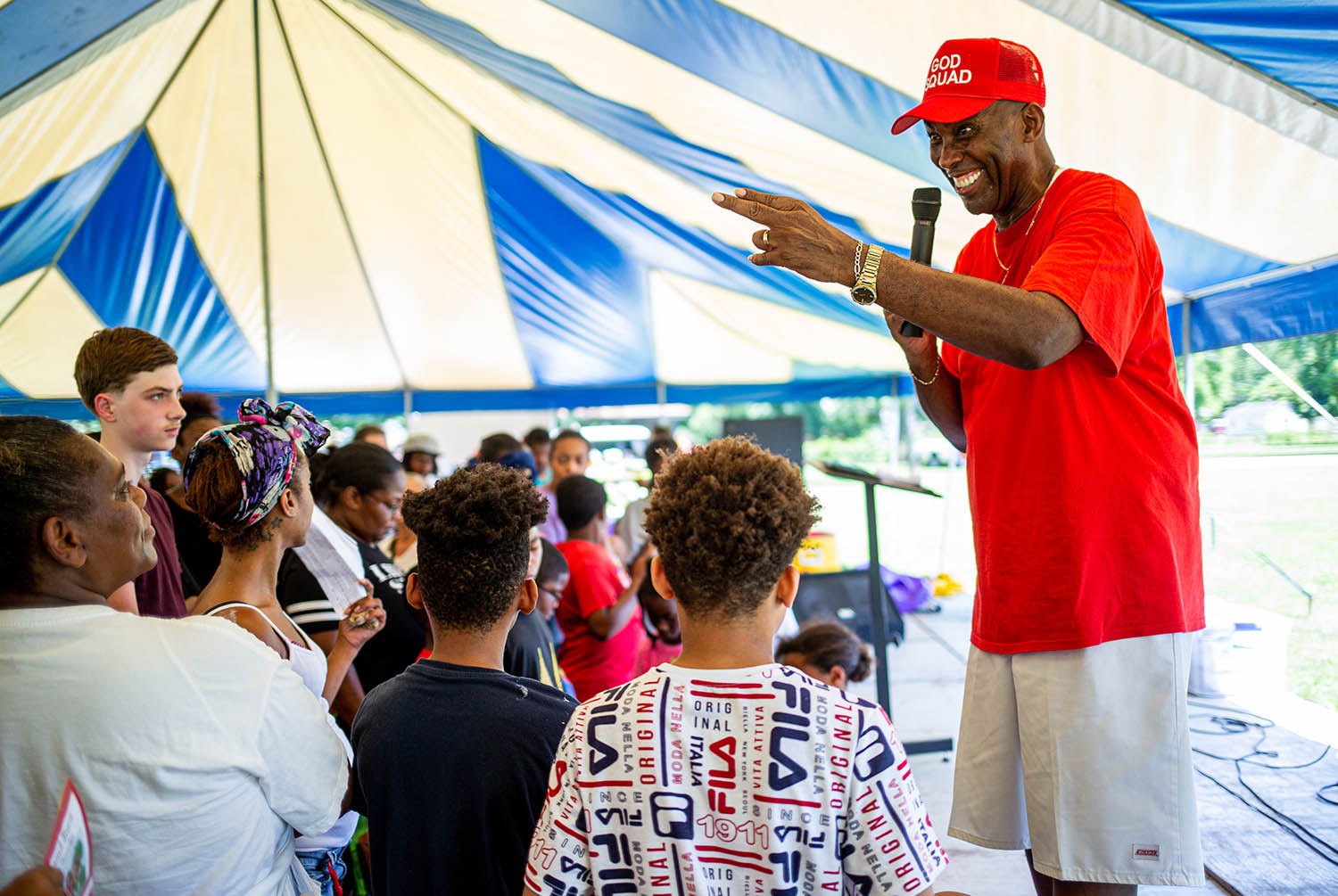 Jessie R. Bates, coordinator of the Stop the Violence Project, asks for attendees to come closer to the stage to pray with them after telling his story of surviving drugs and violence during the Stop the Violence Project's Back to School Block Party Street Festival at Jaycee Park, Saturday, July 13, 2019, in Springfield, Ill. The festival included opportunities with attendees to meet with area social services and also receive free book bags and a box of groceries. [Justin L. Fowler/The State Journal-Register]