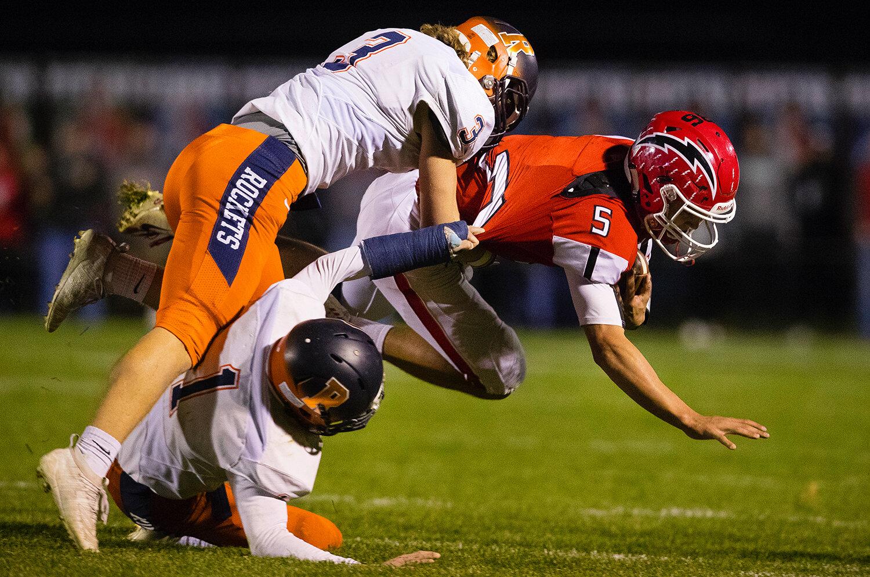 Rochester's Jayden Myren (3)  and Rochester's Logan Peters (1)  bring Glenwood quarterback Luke Lehnen (5) down at Glenwood High School Friday, Oct. 25, 2019. [Ted Schurter/The State Journal-Register]