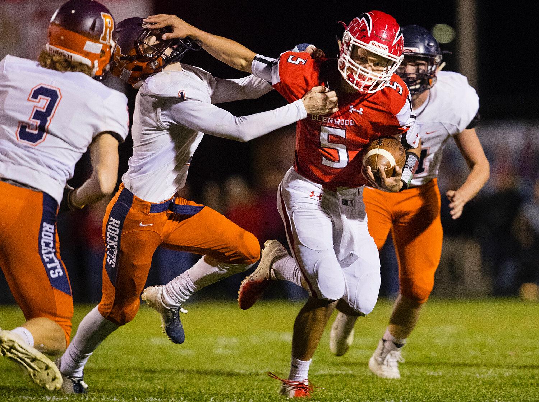 Glenwood quarterback Luke Lehnen (5)  stiff arms Rochester's Logan Peters (1)  as he rushes forward at Glenwood High School Friday, Oct. 25, 2019. [Ted Schurter/The State Journal-Register]