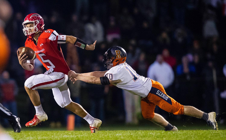 Glenwood quarterback Luke Lehnen (5) escapes from Rochester's Jacob Gunter's grasp at Glenwood High School Friday, Oct. 25, 2019. [Ted Schurter/The State Journal-Register]