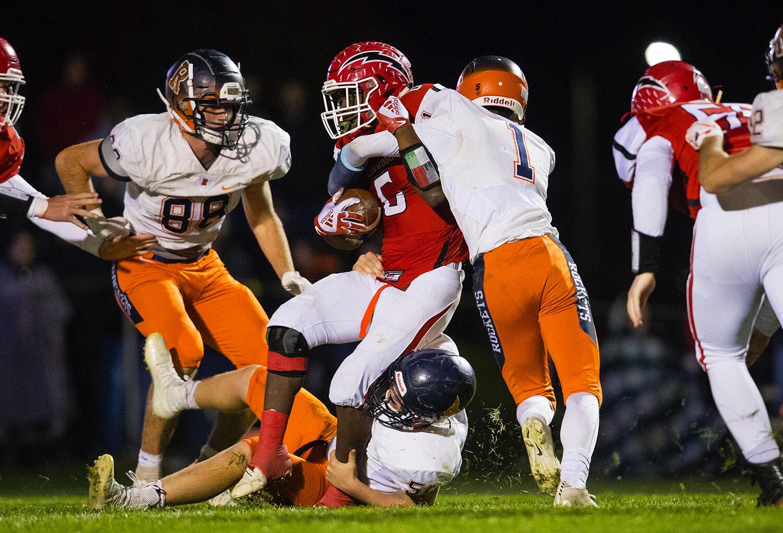A trio of Rochester defenders bring down Glenwood's Narkel LeFlore (6) at Glenwood High School Friday, Oct. 25, 2019. [Ted Schurter/The State Journal-Register]