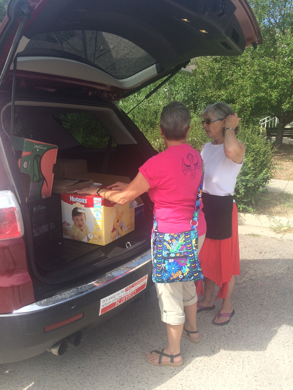 One of our wonderful volunteers, who prefers to remain anonymous, helps staff member Nancy Ott carry in a carload of household goods.