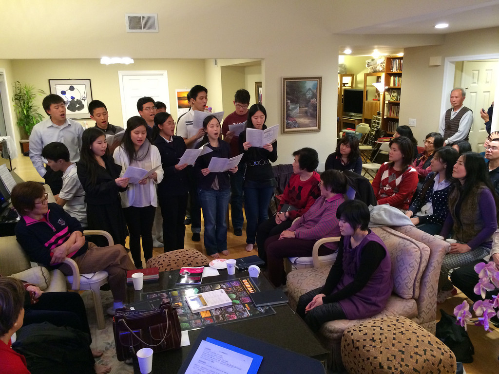 The Youth lead a sing-along at Gospel Night at a member's home.