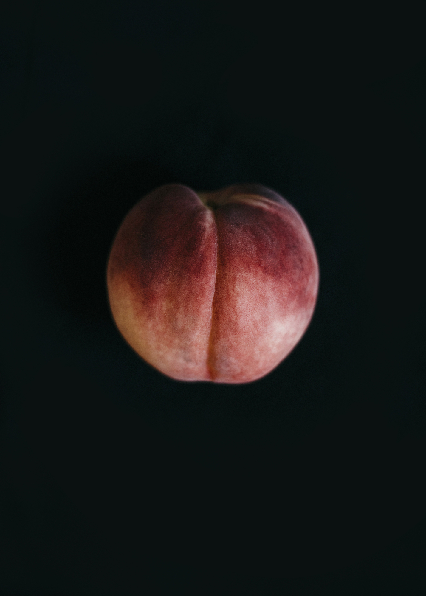 Image of a peach on black by Los Angeles Food Photographer Rebecca Peloquin Photography as part of Dramatic Produce series