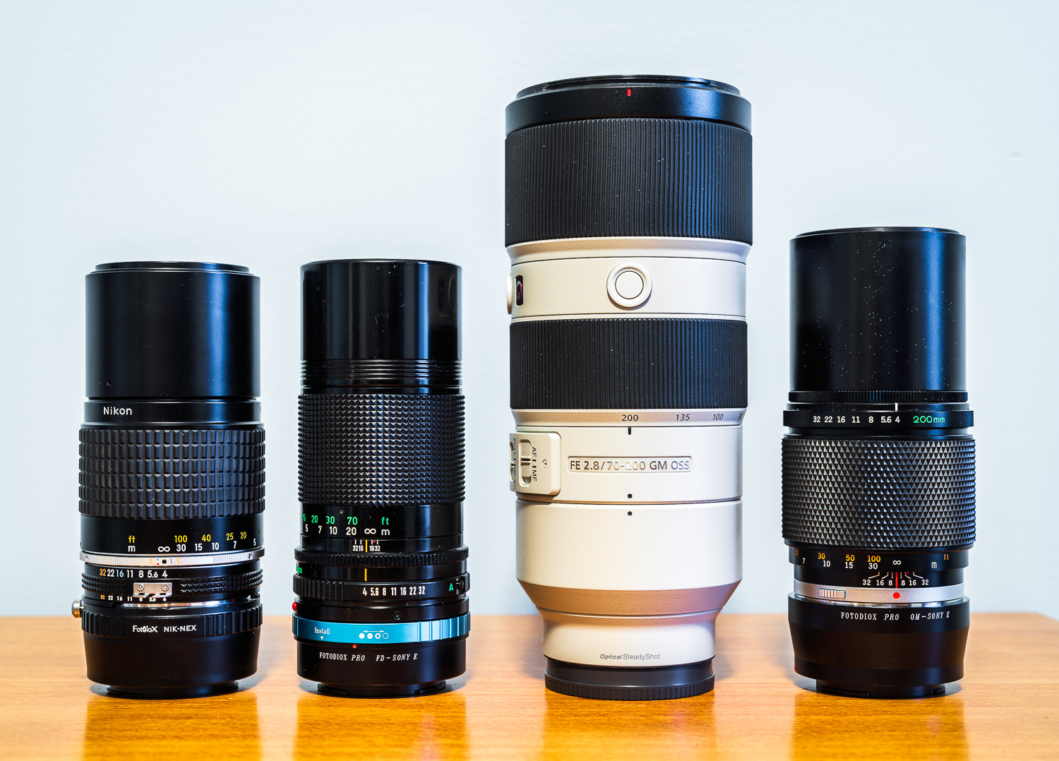 From left to right: Nikon Ai-s Nikkor 200mm f/4 (1.38 lbs), Canon new FD 200mm f/4 (1.20 lbs), Sony 70-200 f/2.8 GM (3.26 lbs), and Olympus OM Zuiko MC Auto-T 200mm f/4 (1.35 lbs)