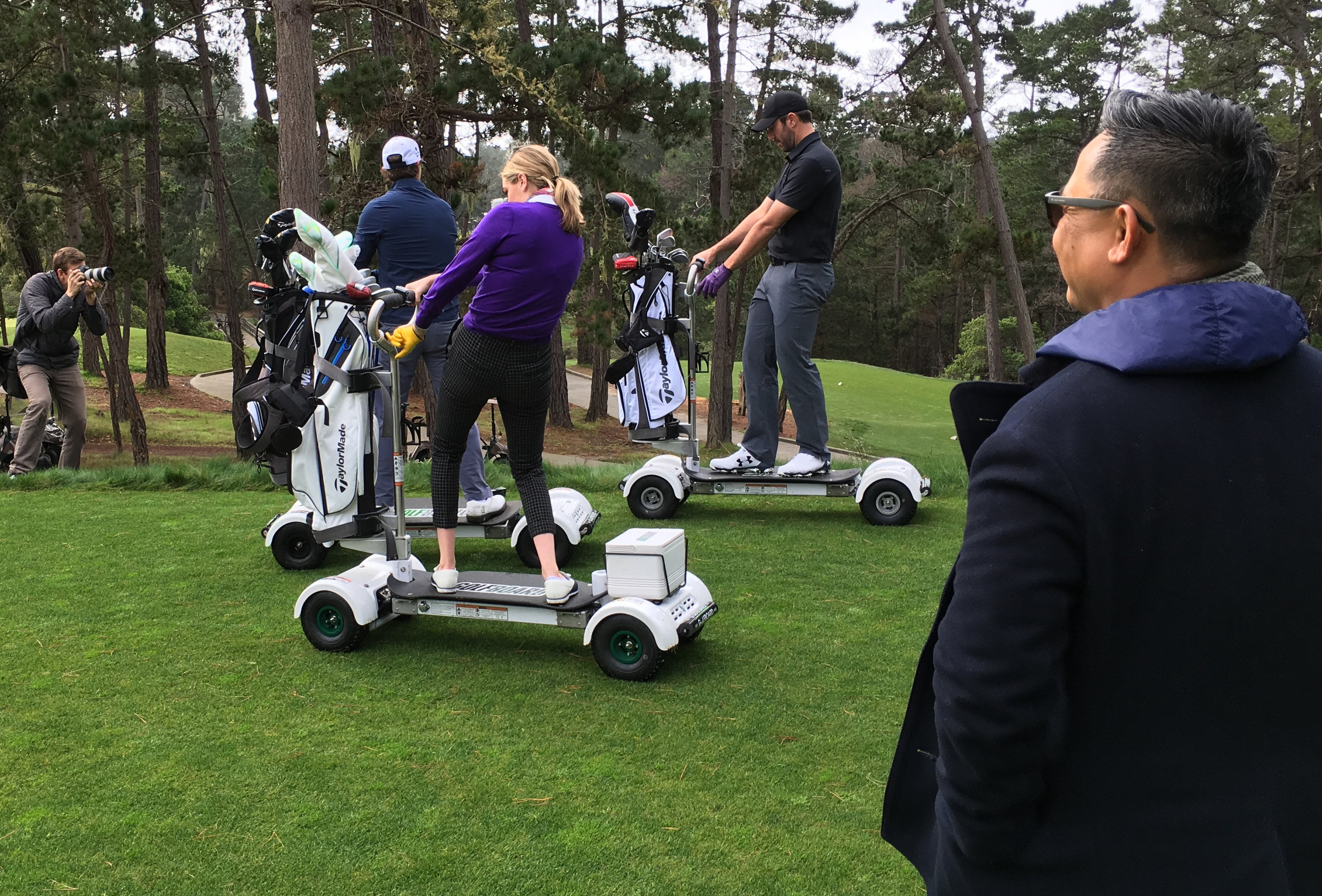 Luan Pham (foreground) looks on as Supermodel Kate Upton, Tigers pitching ace Justin Verlander, and Poppy Hills Director of Performance Jeff Ritter pose for the camera on their GolfBoards.
