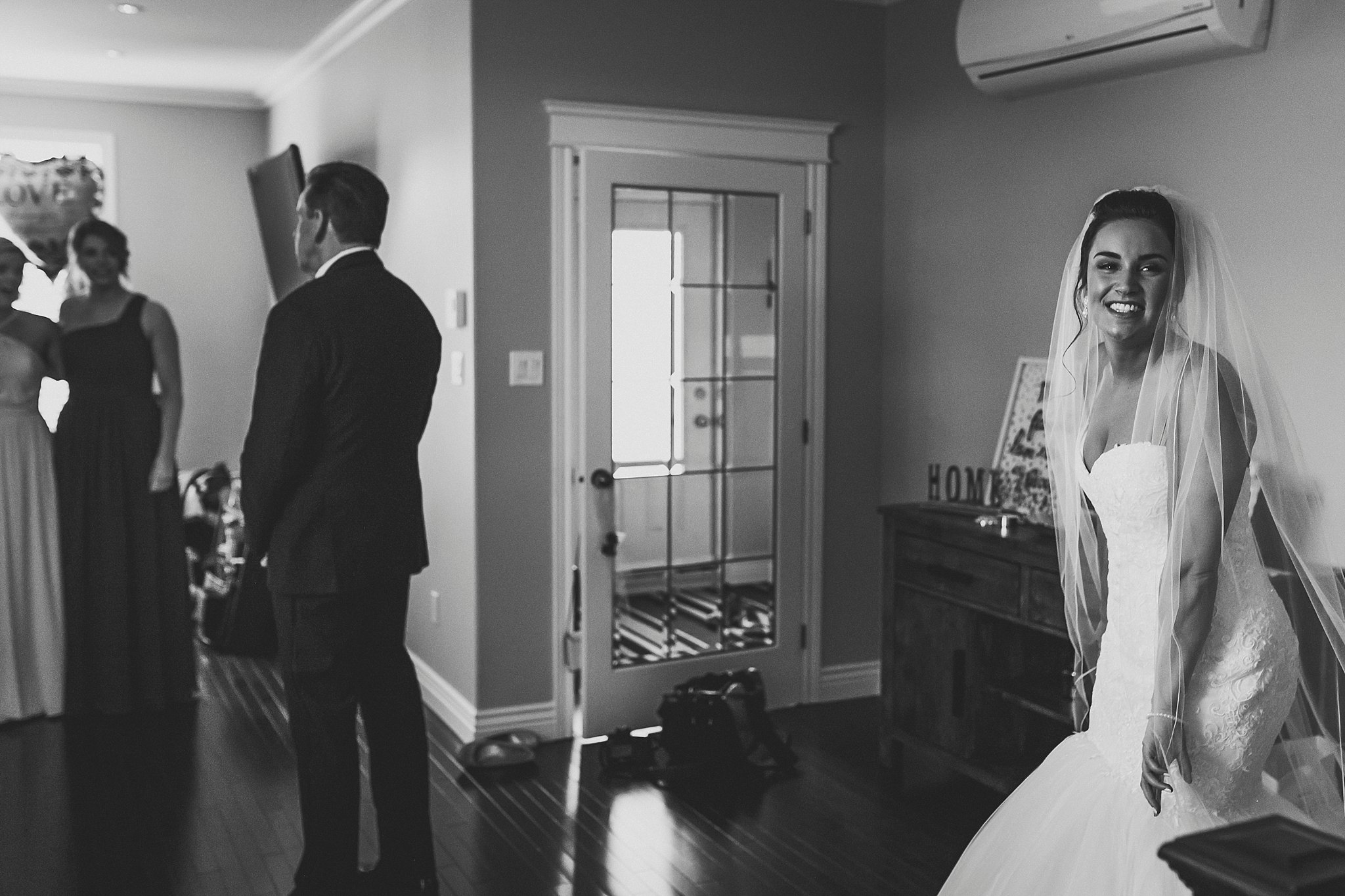 Bride in her Maggie Sottero wedding dress from The Model Shop in St. John's, NL waits for dad to see her.