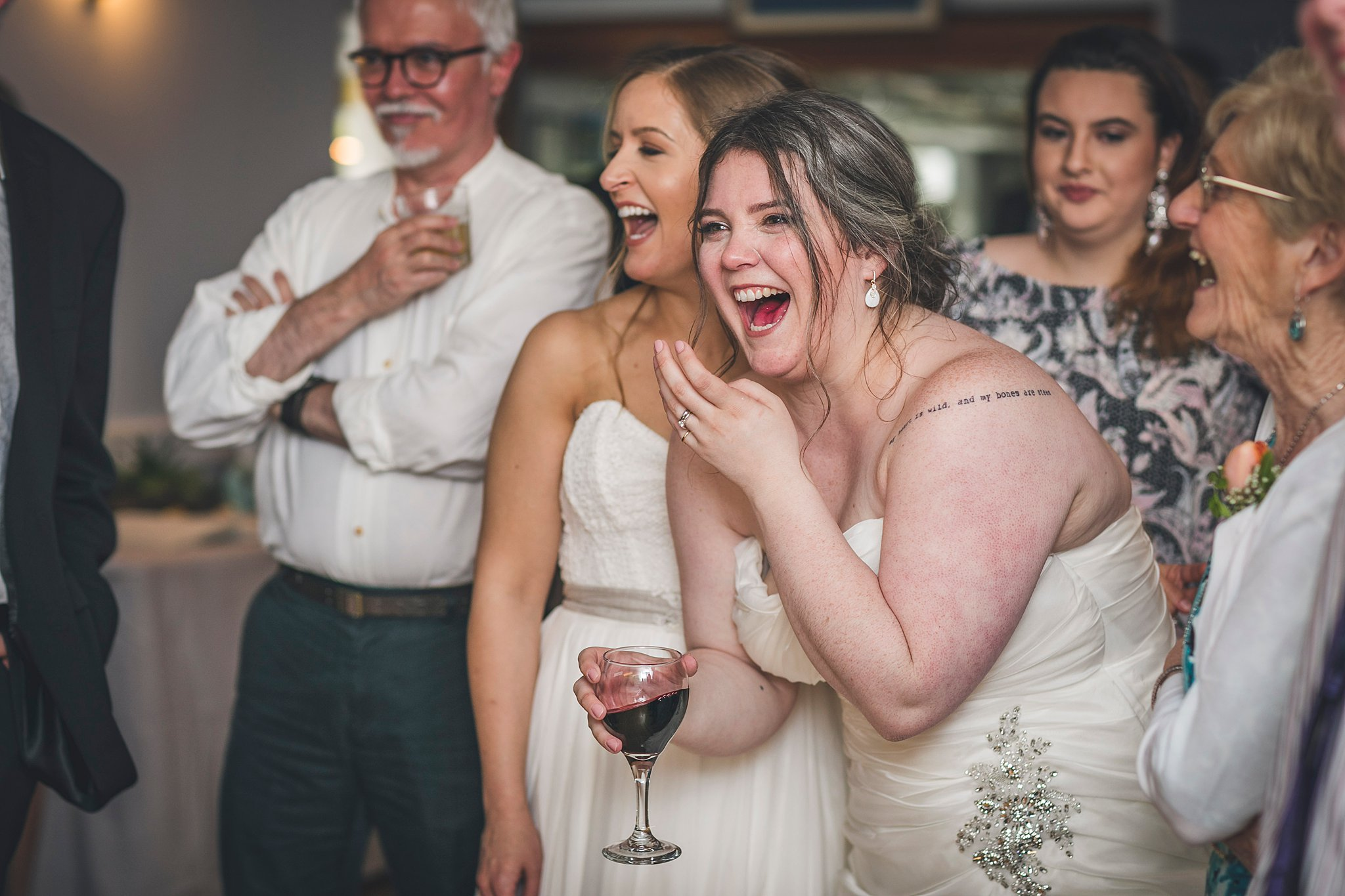 Brides laugh during their wedding reception held at Murray's Pond in Newfoundland