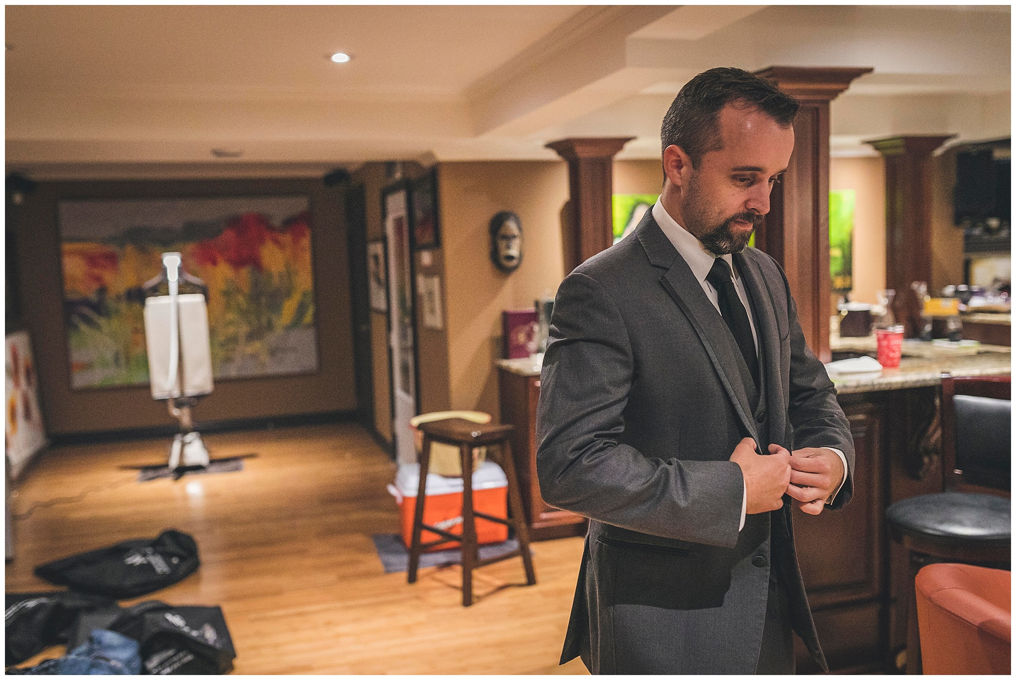 Groom adjusts his suit jacket prior to his wedding