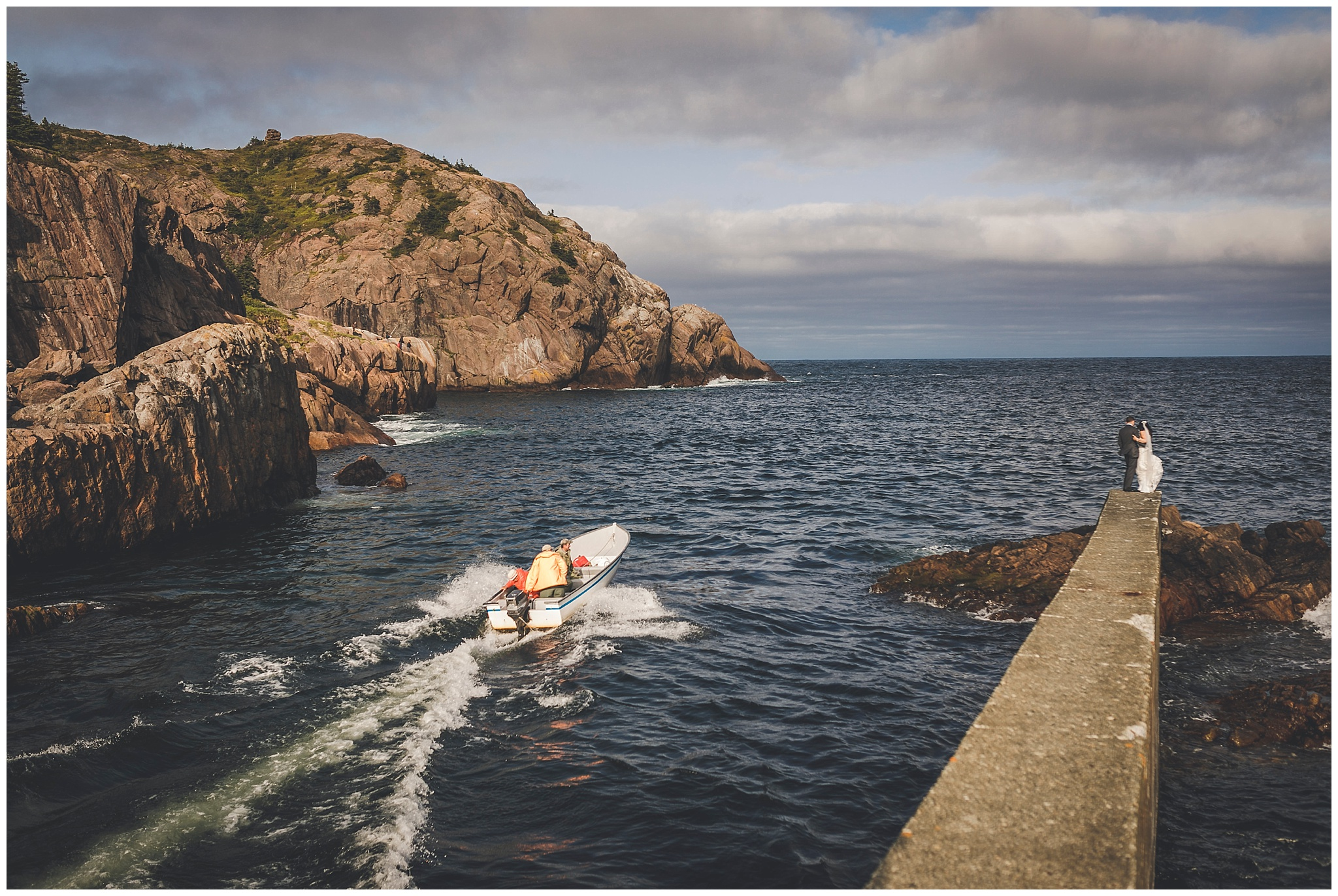 Local fisherman head past a bride and groom in Quidi Vidi