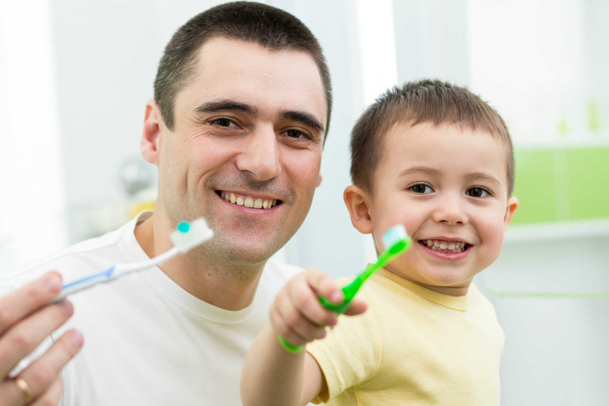 Brushing teeth with father and child, son, Dr. Nguyen V. Nguyen, DMD DDS, Magnolia Dental, Dentist, Orlando, Waterford Lakes, Avalon Park, Alafaya, Colonial, Cosmetic, Family, Pediatric, Implant, Braces, Orthodontics, Best, Cone beam CT, Emergency, Dentures, Veneers, Zoom Whitening
