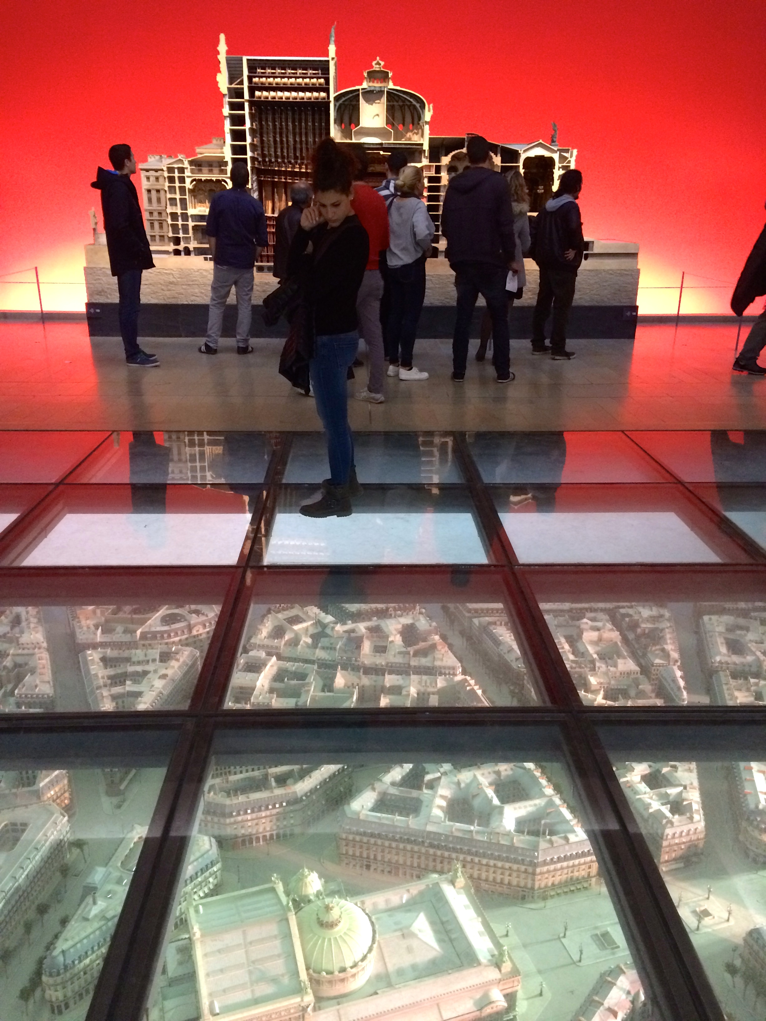 Visitors peer downward at a large model of the Opera neighbourhood beneath a glass floor for context.