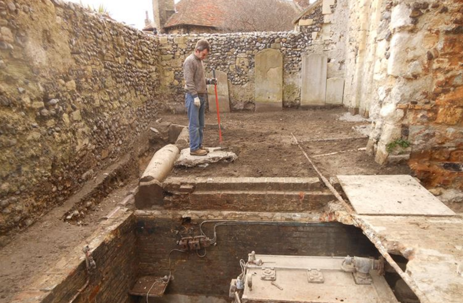 Volunteer digger Gareth inspects the 20th century heating plant which has been left exposed and will be removed allowing space to construct toilets
