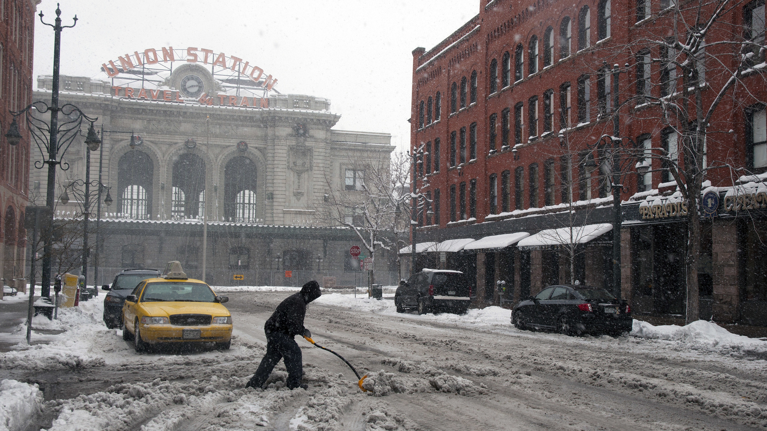 A man clears snow on Denver's 17th Street during a blizzard. By the time the snow stopped, nearly a foot and a half of snow blanketed the city.