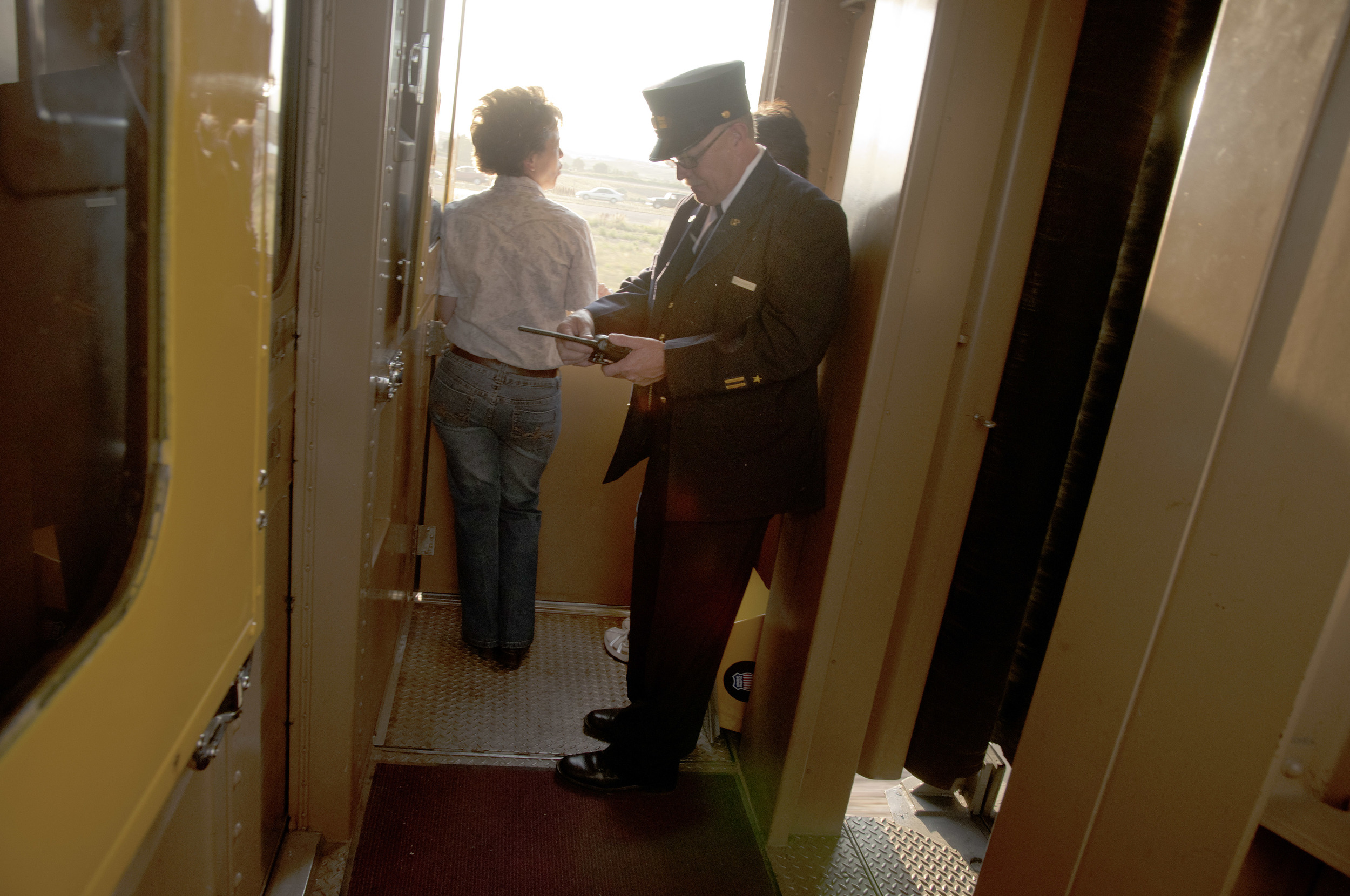 A Union Pacific conductor checks his radio momentarily in the vestibule aboard the Denver Post's Cheyenne Frontier Days passenger special train as it chugs across northern Colorado. The vintage carriages were brought in specially for this run, and date from the era of steam trains.
