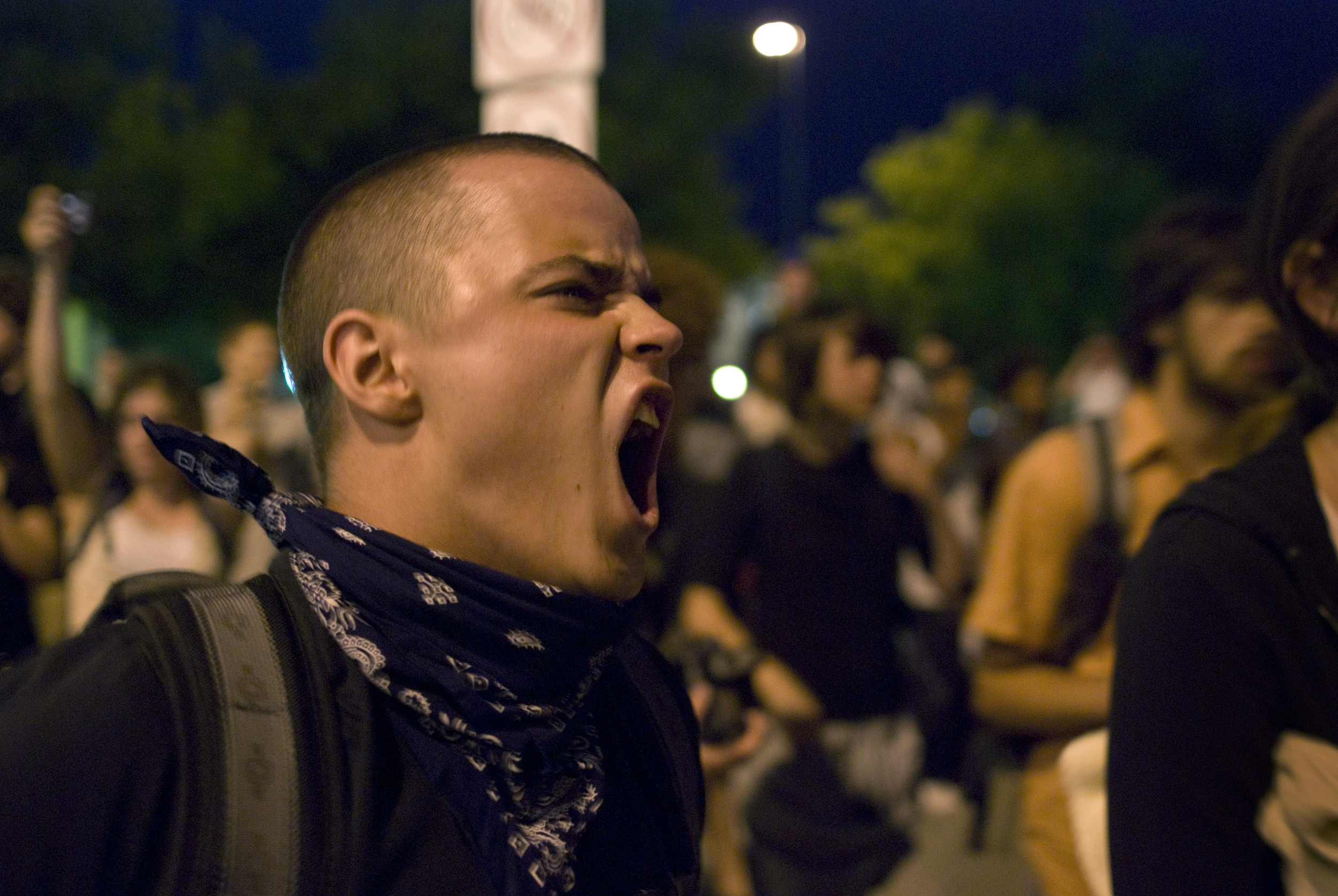 A protester on 15th Street shouts back at the three-deep line of Denver Police around 9:30PM on night one of the 2008 Democratic National Convention.