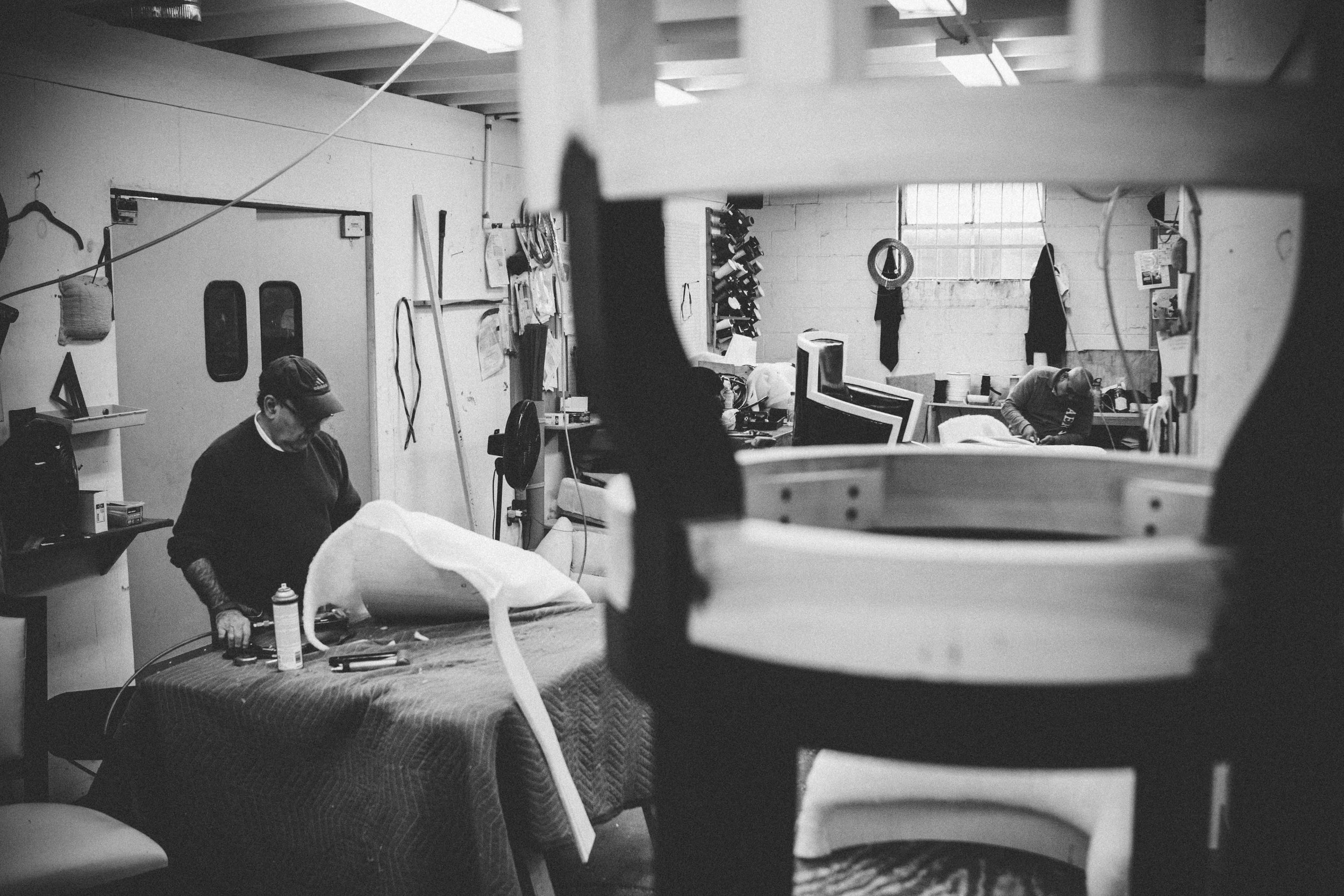 Part of the upholstery shop in use while one piece awaits its turn to have a cushy seat crafted.
