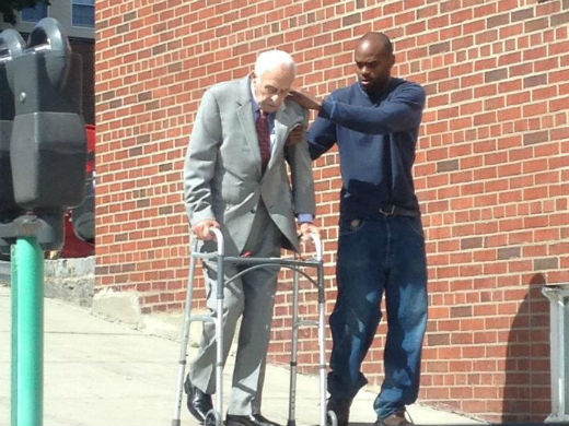 A young man helping an older gentleman walk down a steep slope