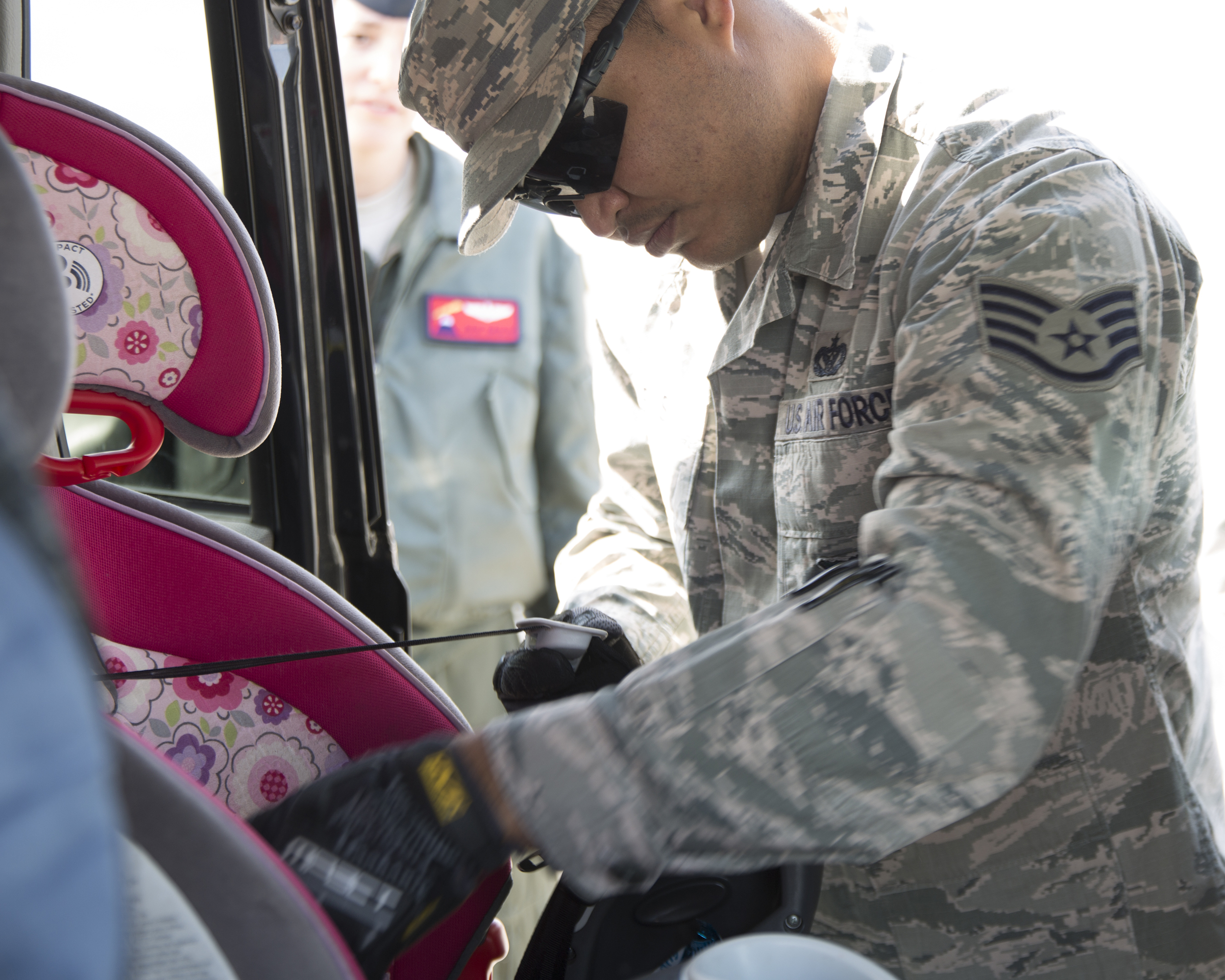Staff Sgt. Trevor Alexis, 374th Civil Engineer Squadron fire department NCO in charge of training, inspects a child safety seat for a driver at Yokota Community Center, March 4, 2015. Alexis is a certified child passenger safety technician. (U.S. Air Force photo by Osakabe Yasuo/Released)