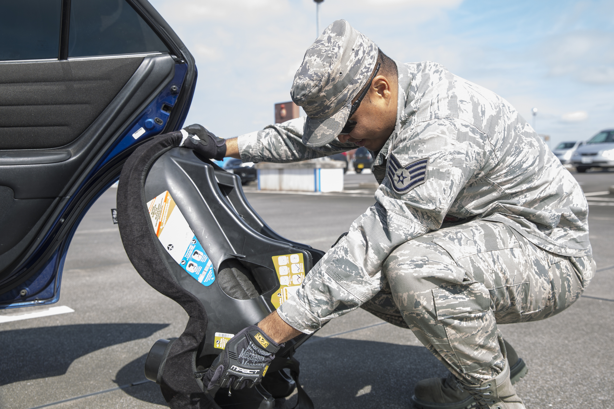 Staff Sgt. Trevor Alexis, 374th Civil Engineer Squadron fire department NCO in charge of training, helps install a child safety seat for a driver at Yokota Community Center, March 4, 2015. Alexis is a certified child passenger safety technician. (U.S. Air Force photo by Osakabe Yasuo/Released)