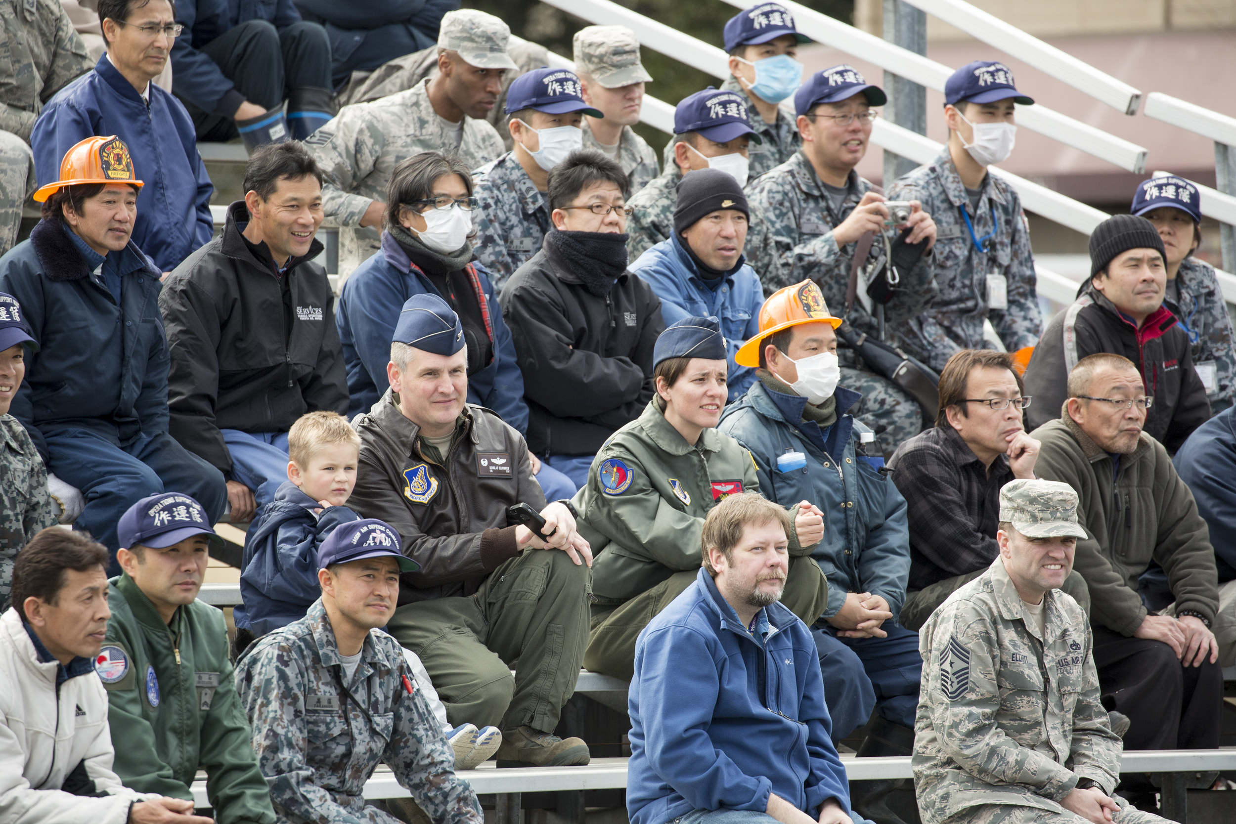 """Audience members watch the traffic safety demonstration by stunt project team """"Super Drivers"""" during the safety festival at Yokota Air Base, Japan, March 6, 2015. The event demonstrated hairy moments in car accidents. (U.S. Air Force photo by Osakabe Yasuo/Released)"""
