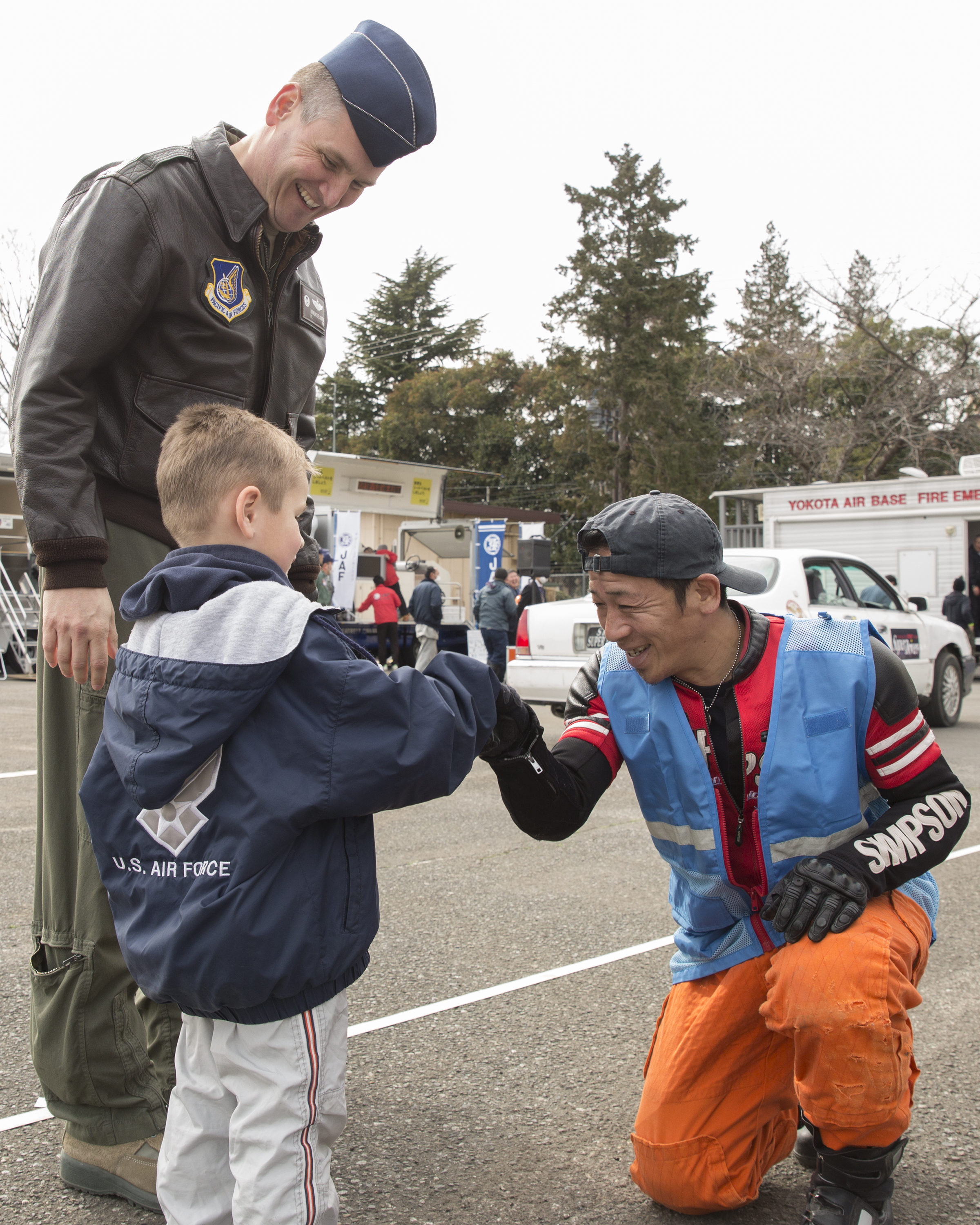 """Col. Douglas DeLaMater, 374th Airlift Wing commander, and his son, Christian, greet a member from the stunt project team """"Super Drivers"""" after a traffic safety demonstration at Yokota Air Base, Japan, March 6, 2015. The 374th Airlift Wing Safety provided Yokota residents with various events such as a Tokyo Metropolitan Police Department motorcycle unit demonstration, traffic safety demonstration, earthquake and smoke house, firefighting experience, fire ladder trucks experience, 374th Security Forces Squadron patrol vehicle ride, seatbelt simulator and child car seat checks. (U.S. Air Force photo by Osakabe Yasuo/Released)"""