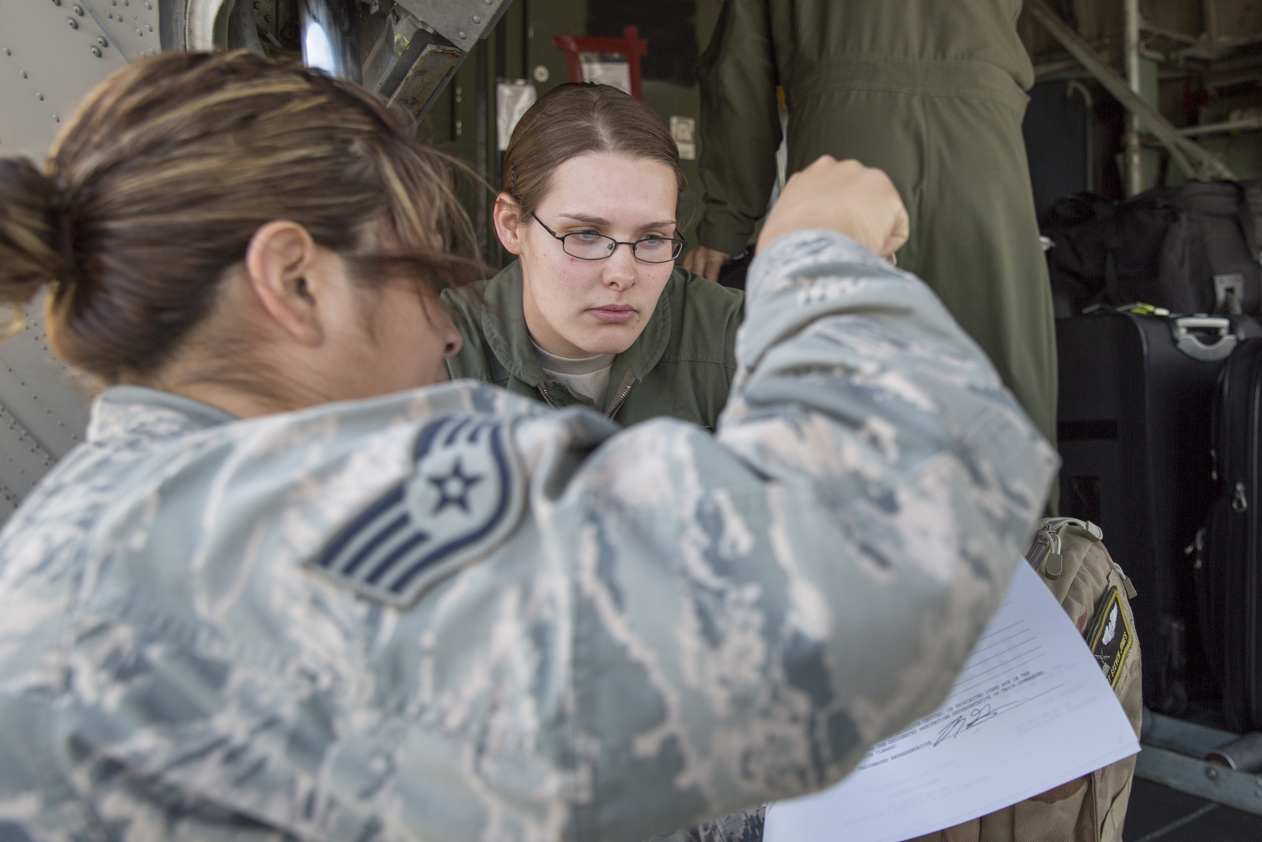 (Left and right) Staff Sgt. Isabell Hood, 374th Logistics Readiness Squadron, and Senior Airman Taylor Hubstenberger, 36th Airlift Squadron loadmaster, check documents at Yokota Air Base, Japan, May 5, 2015. Airmen departed to conduct humanitarian assistance and disaster relief operations in support of the Government of Nepal in the wake of a 7.8 magnitude earthquake that devastated many regions of the country on April 25, 2015. (U.S. Air Force photo by Osakabe Yasuo/Released)