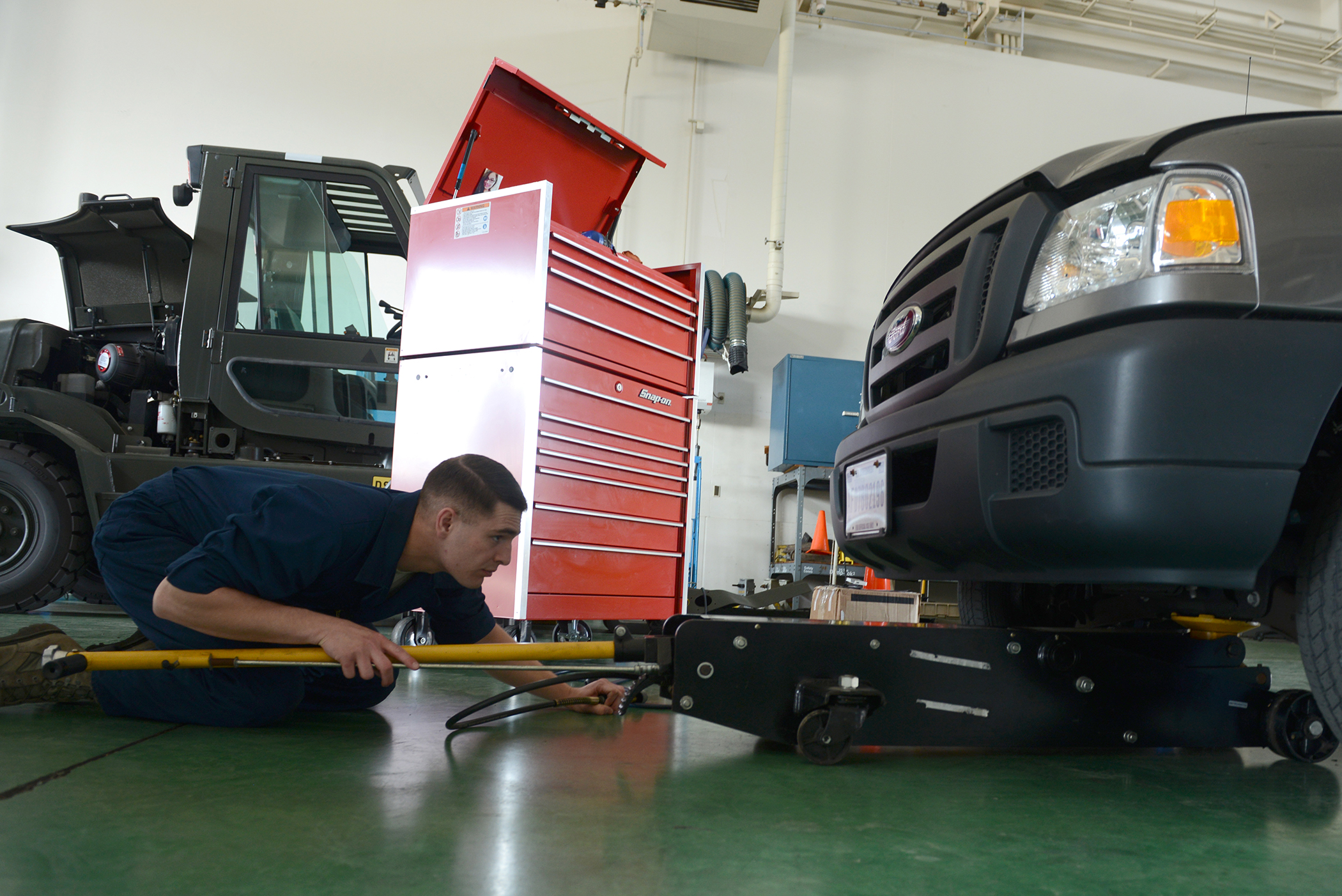 Senior Airman Brandon Higginbotham, 374th Logistics Readiness Squadron vehicle maintenance journeyman, positions a jack under a government vehicle at Yokota Air Base, Japan, April 28, 2015. The truck was brought into the vehicle maintenance shop to assess the front brakes. (U.S. Air Force photo by Airman 1st Class David C. Danford/Released)
