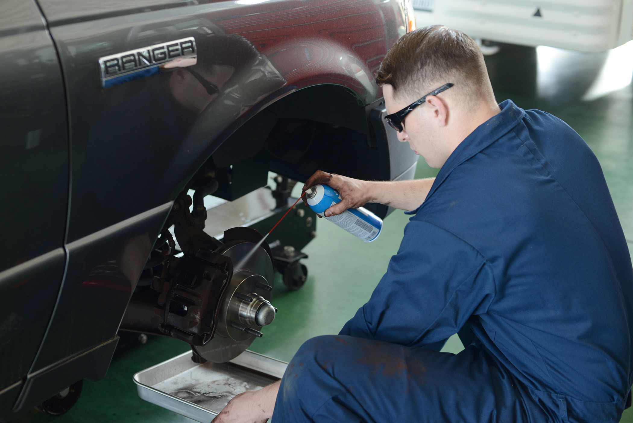 Senior Airman Brandon Higginbotham, 374th Logistics Readiness Squadron vehicle maintenance journeyman, sprays break cleaner to remove manufacturing oils from a new rotor at Yokota Air Base, Japan, April 28, 2015. Removing the oils prevents damage to the pads and rotor. (U.S. Air Force photo by Airman 1st Class David C. Danford/Released)