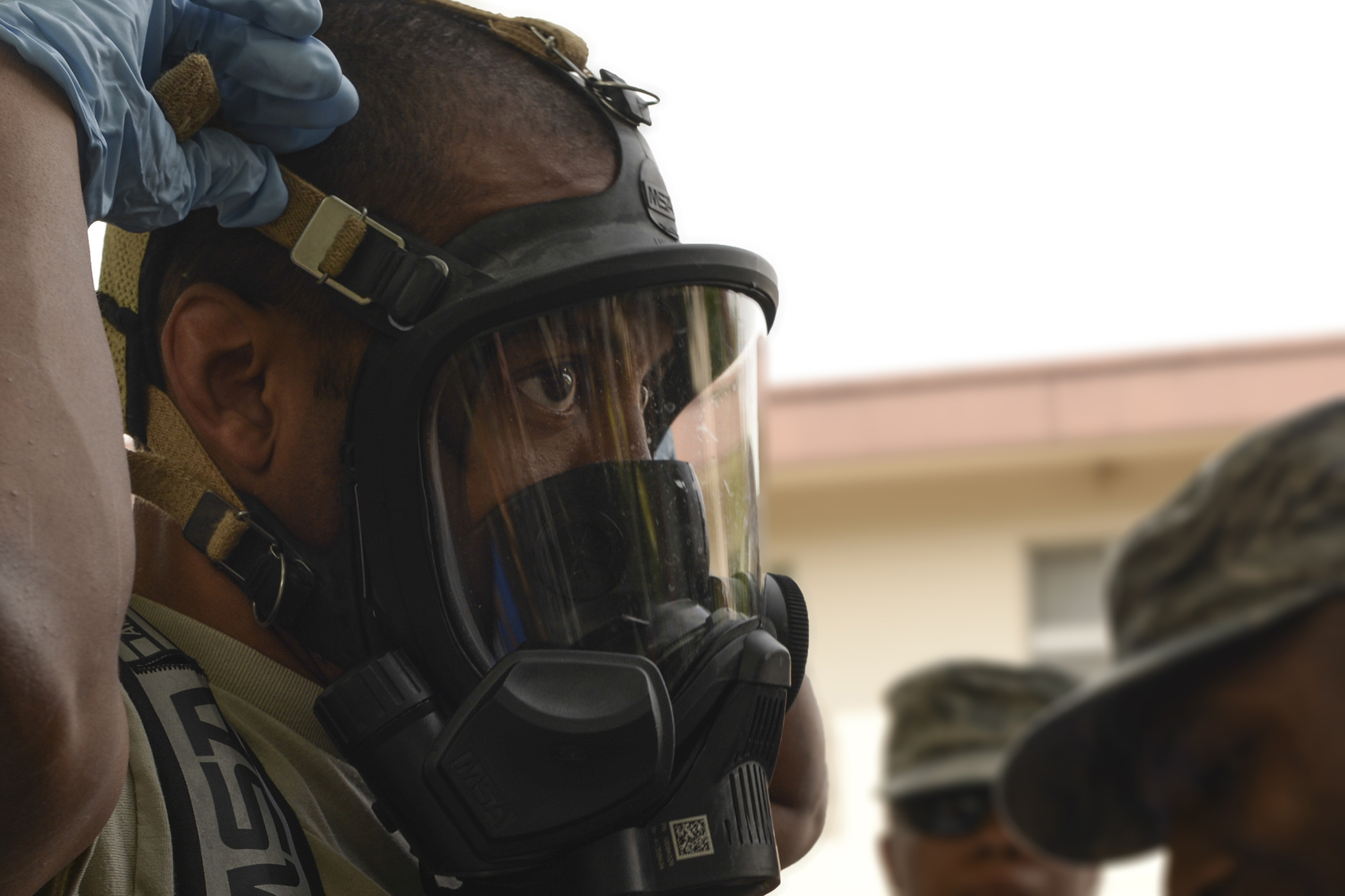 Staff Sgt. Sheraz Cedeno, 374th Civil Engineer Squadron NCO in charge of emergency management and operations, tightens his chemical mask before entering the scene of a mock environmental hazard, May 6, 2015, at Yokota Air Base, Japan. Participants practiced responding to a training scenario involving a passed out resident inside base housing. (U.S. Air Force photo by Airman 1st Class Elizabeth Baker/Released)