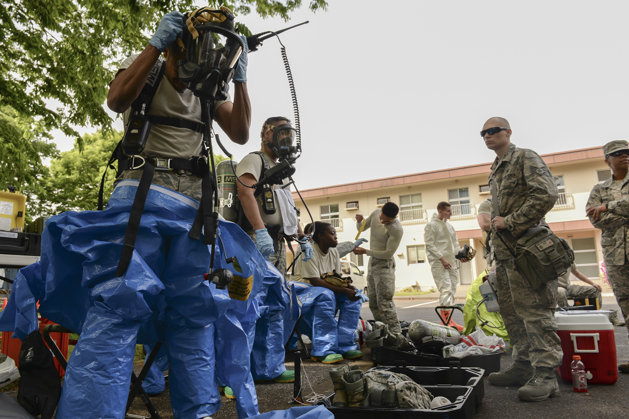 Airmen from the 374th Civil Engineer Squadron and the 374th Aerospace Medicine Squadron suit up to respond to a mock chemical threat, May 6, 2015, at Yokota Air Base, Japan. The chemical threat was part of an environmental hazard exercise performed to keep emergency responders adept on responding to life-threatening events. (U.S. Air Force photo by Airman 1st Class Elizabeth Baker/Released)