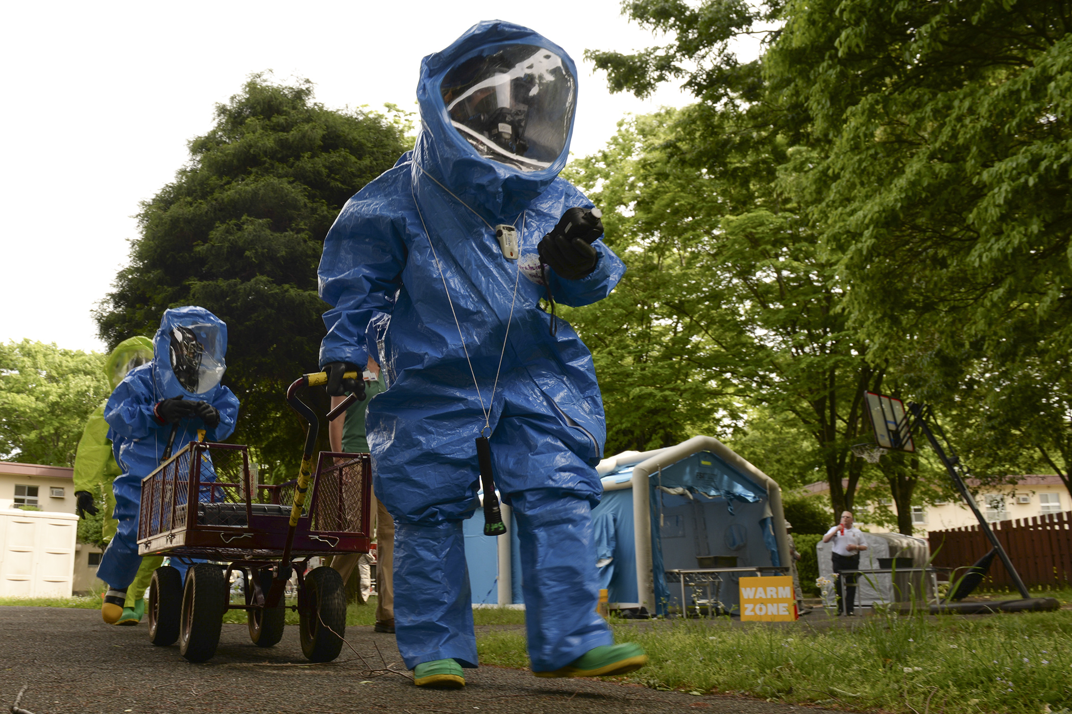 Airmen from the 374th Civil Engineer Squadron and the 374th Aerospace Medicine Squadron move toward to the scene of a mock chemical threat, May 6, 2015, at Yokota Air Base, Japan. According to the training scenario, responders were called to investigate after a simulated resident was discovered passed out in base housing. (U.S. Air Force photo by Airman 1st Class Elizabeth Baker/Released)
