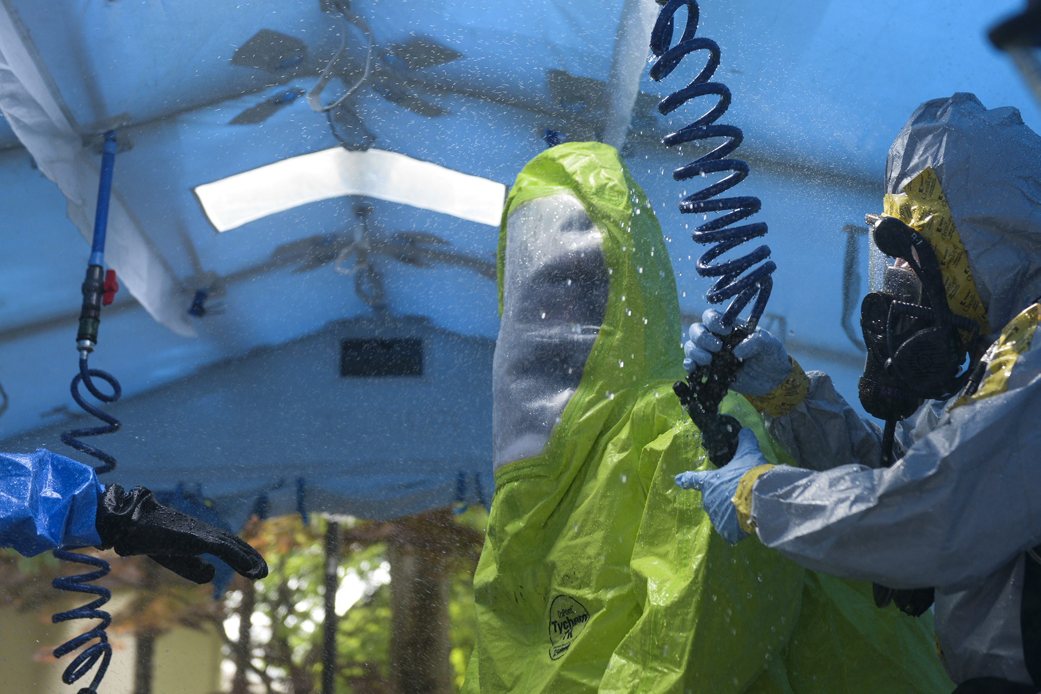 Senior Airman Craig Deacon, left, 374th Civil Engineer Squadron driver operator, passes through a decontamination shower tent, May 6, 2015, at Yokota Air Base, Japan. Emergency responders passed through the tent after coming into contact with simulated hazardous materials. (U.S. Air Force photo by Airman 1st Class Elizabeth Baker/Released)