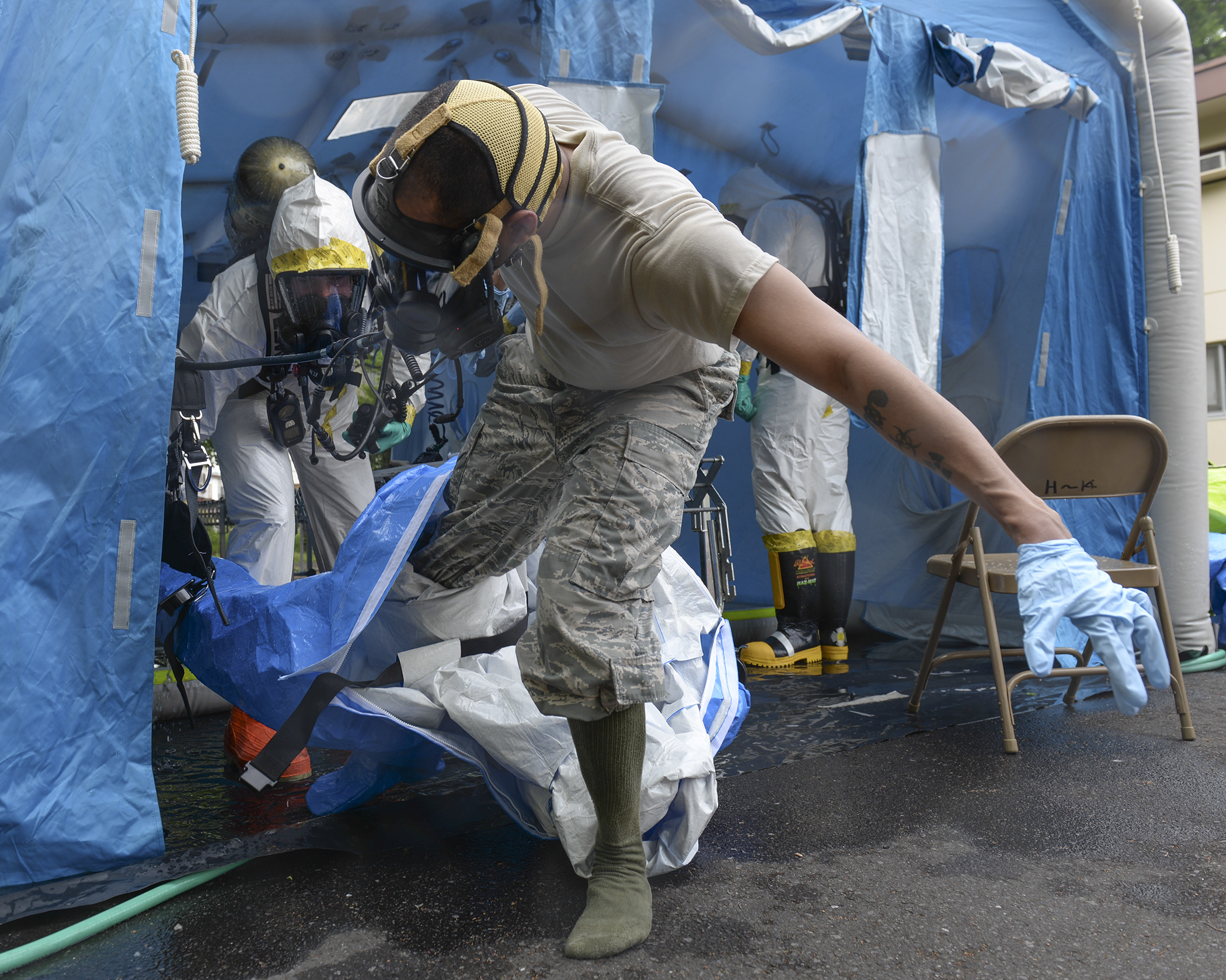 Staff Sgt. Sheraz Cedeno, 374th Civil Engineer Squadron NCO in charge of emergency management and operations, steps out of a protective suit after completing a mock chemical threat training scenario, May 6, 2015, at Yokota Air Base, Japan. Cedeno was part of a three-man team, which investigated a simulated environmental hazard scenario inside base housing. (U.S. Air Force photo by Airman 1st Class Elizabeth Baker/Released)
