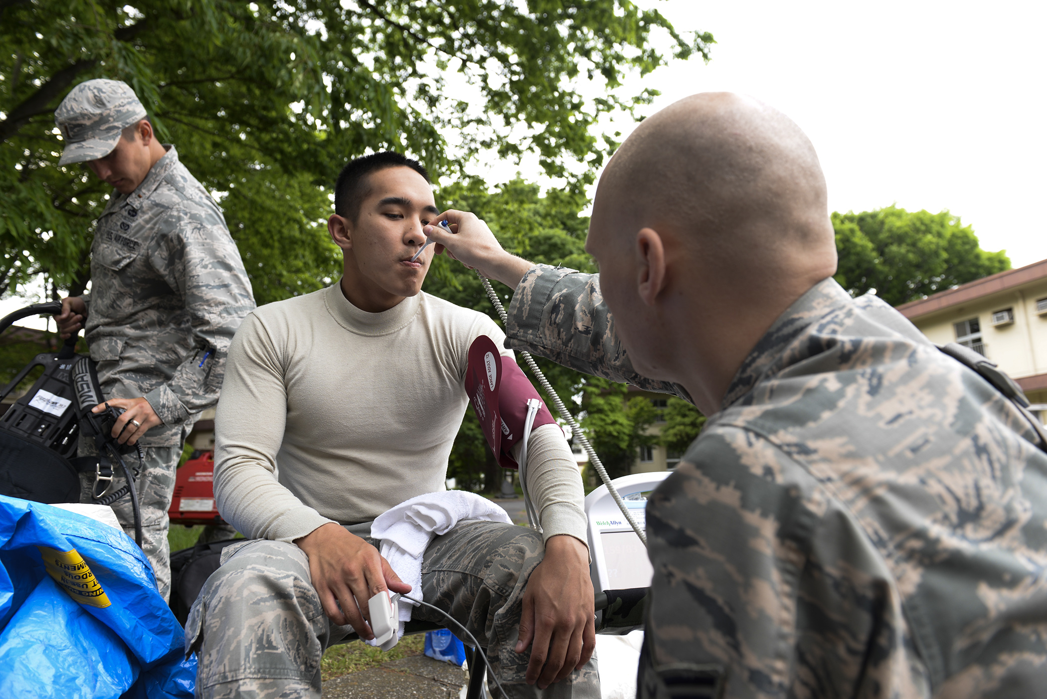 Staff Sgt. Benjamin Smith, right, 374th Aerospace Medicine Squadron NCO in charge of the flight medicine clinic, takes vitals from Senior Airman Vonfernan Carios, 374 AMDS bioenvironmental engineering technician, May 6, 2015, at Yokota Air Base, Japan. Emergency responders were examined after performing under potentially stressful and harmful conditions at the scene of a mock environmental hazard. (U.S. Air Force photo by Airman 1st Class Elizabeth Baker/Released)