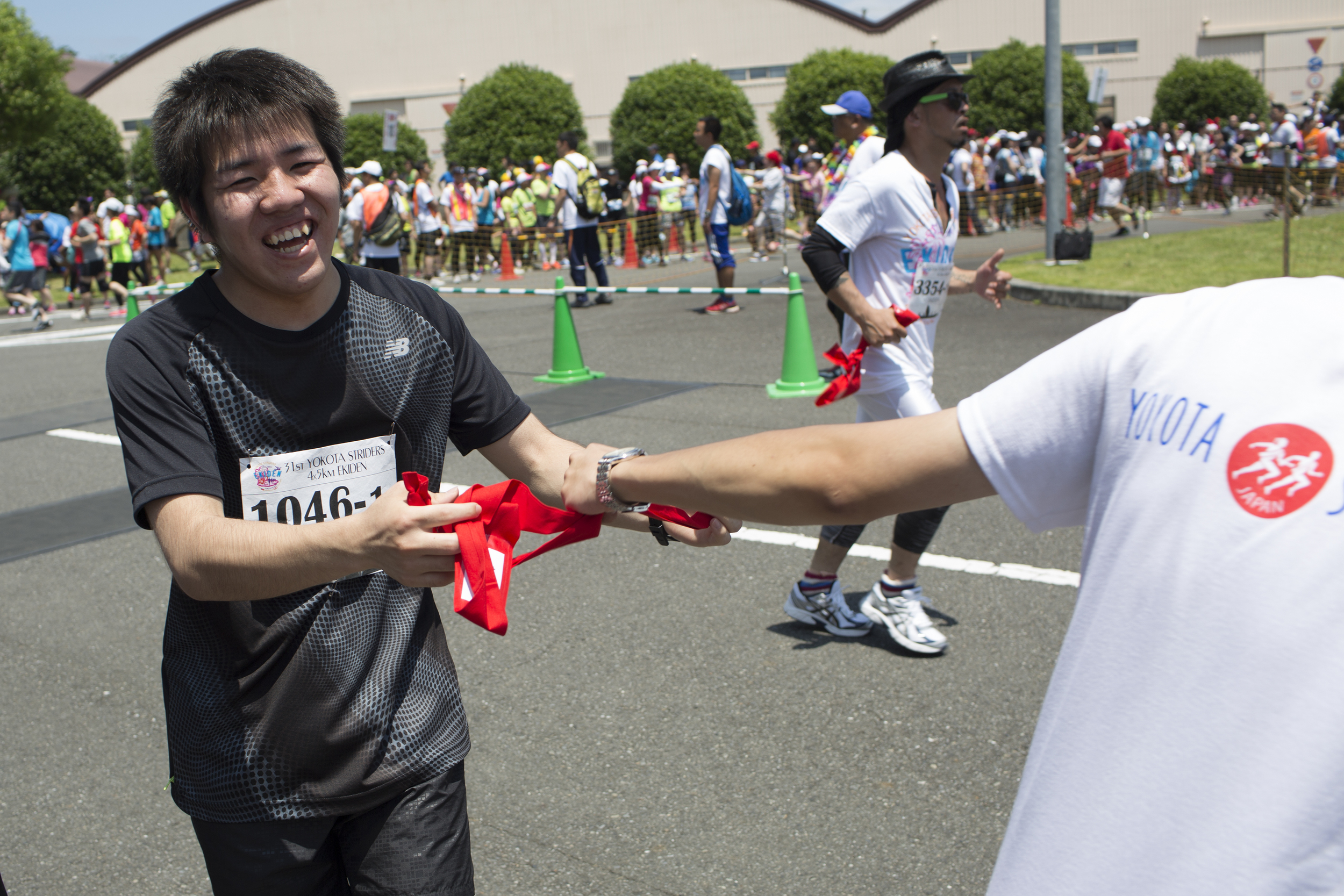 An Ekiden runner hands off a tasuki, a cloth sash, to the next runner during the 31st Annual Ekiden race at Yokota Air Base, Japan. More than 5,800 runners participated in the event sponsored by the Yokota Striders Running Club. (U.S. Air Force photo by Osakabe Yasuo/Released)