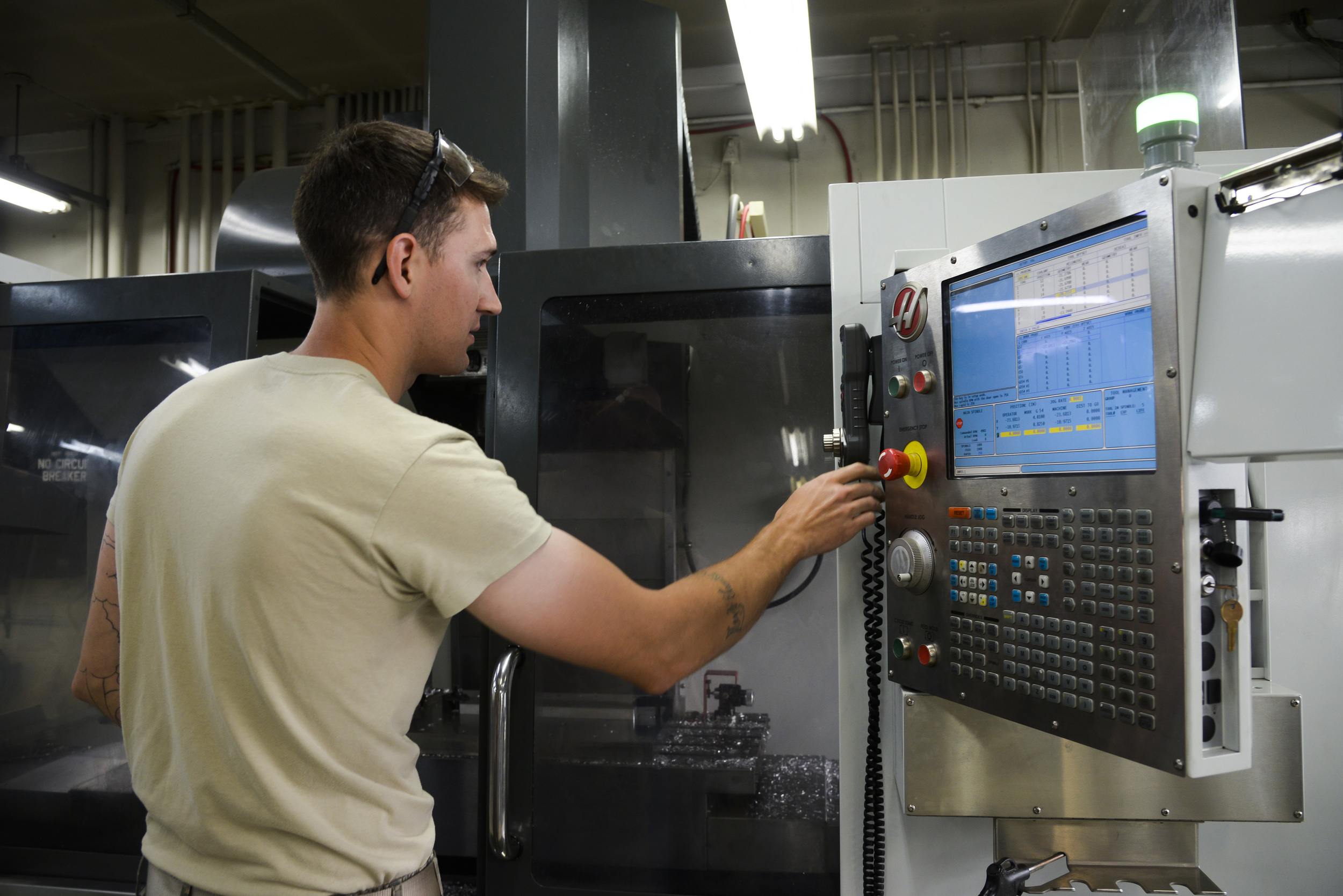 Senior Airman Justin Weeks, 374th Maintenance Squadron aircraft metals technology journeyman, inputs information into the computer numeric controller router to create a C-130 Hercules part in the fabrication shop at Yokota Air Base, Japan, June 23, 2015. Numerical control is the automation of machine tools that are operated by precisely programmed commands encoded on a storage medium. (U.S. Air Force photo by Senior Airman David Owsianka/Released)