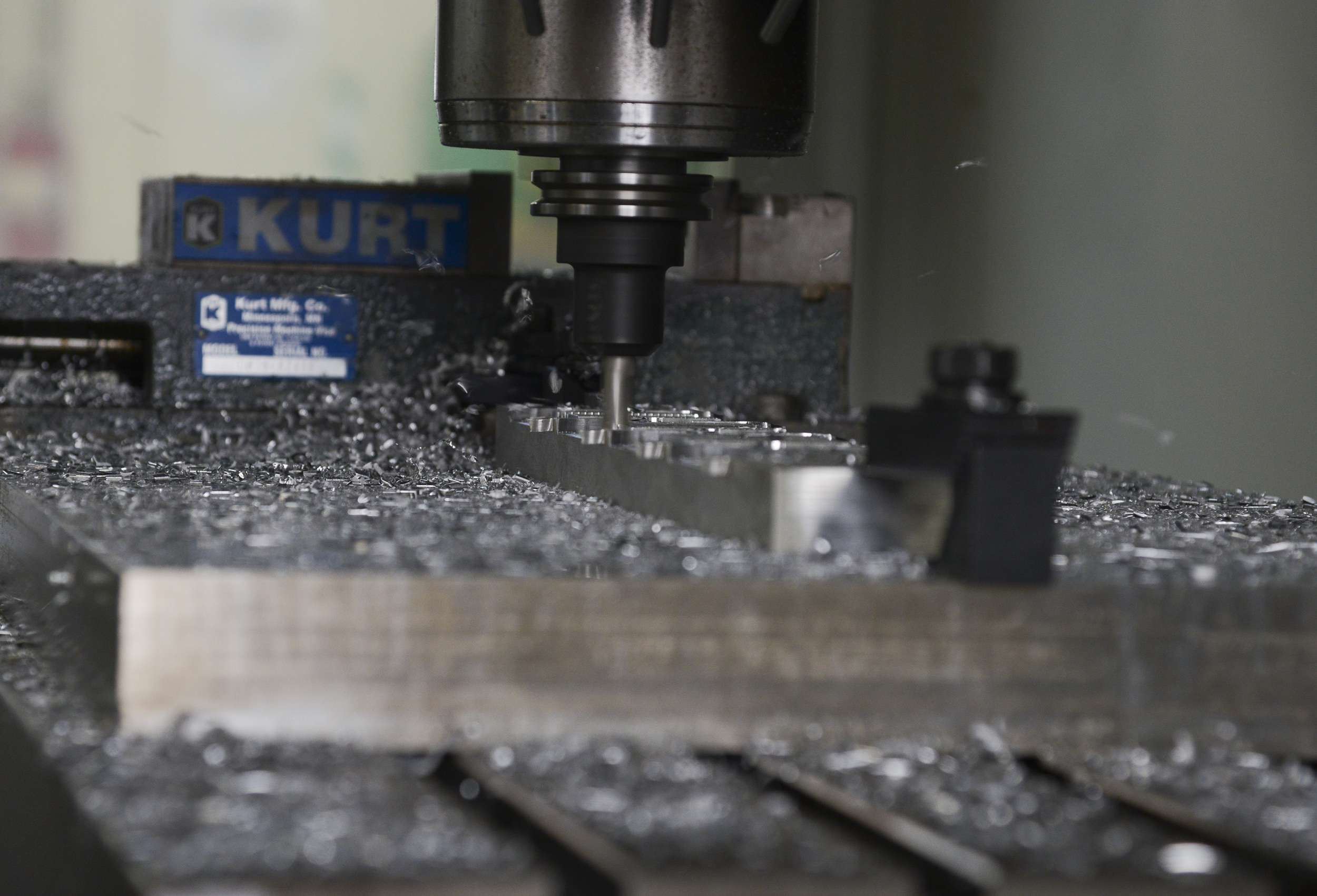 A computer numeric controller router creates a C-130 Hercules crew door arm clamp in the fabrication shop at Yokota Air Base, Japan, June 23, 2015. A CNC router is a computer controlled cutting machine related to the hand held router used for cutting various hard materials, such as wood, composites, aluminium, steel, plastics and foams. (U.S. Air Force photo by Senior Airman David Owsianka/Released)