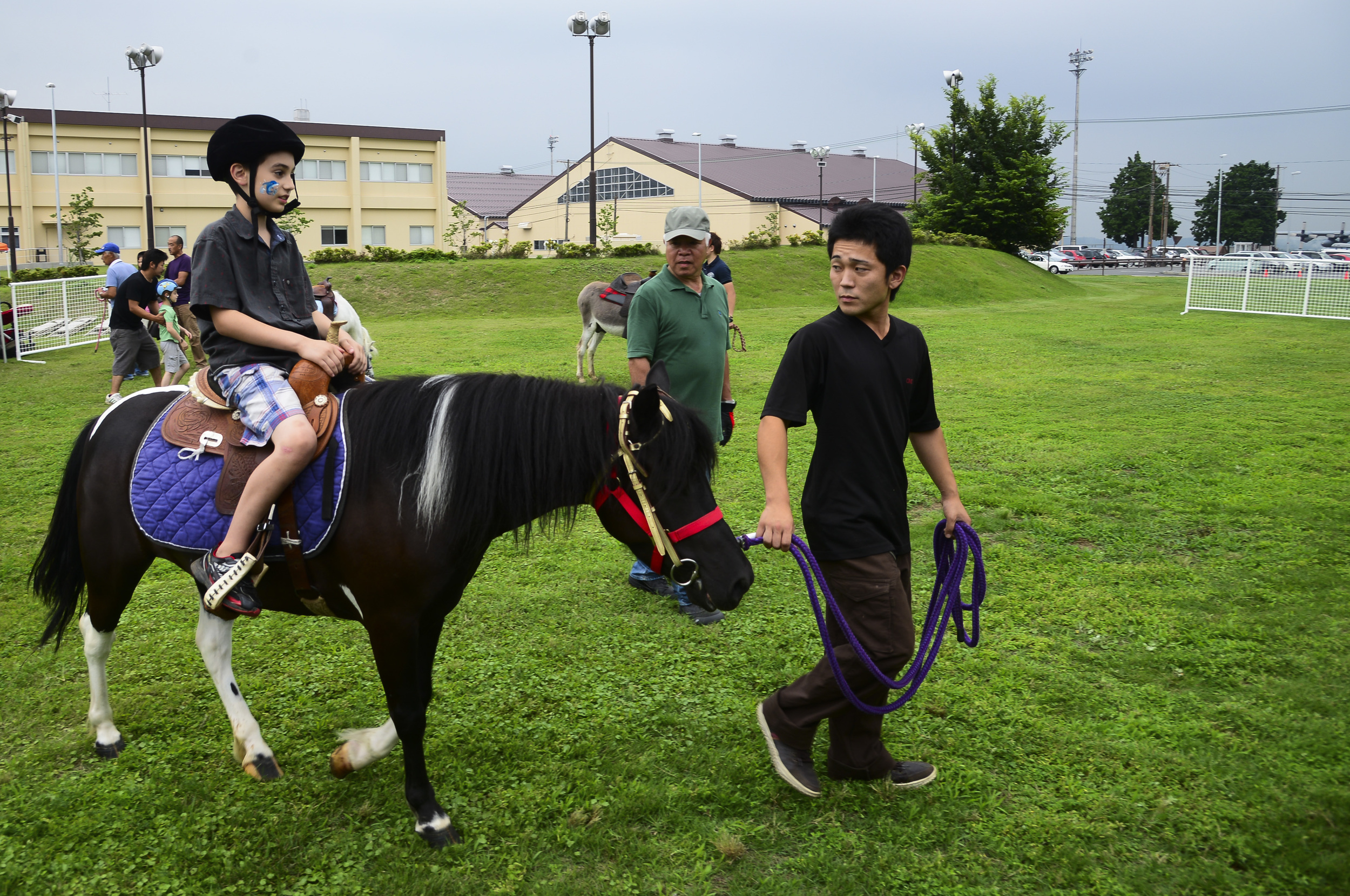Radek Hungler, 9, son of David Hungler, 374th Office of Special Investigations special agent, rides a pony during the Celebrate America event at Yokota Air Base, Japan, July 2, 2015. The annual event provided military members and their families the opportunity to enjoy games, food and bands before culminating in a fireworks display to celebrate Independence Day. (U.S. Air Force photo by Senior Airman David Owsianka/Released)