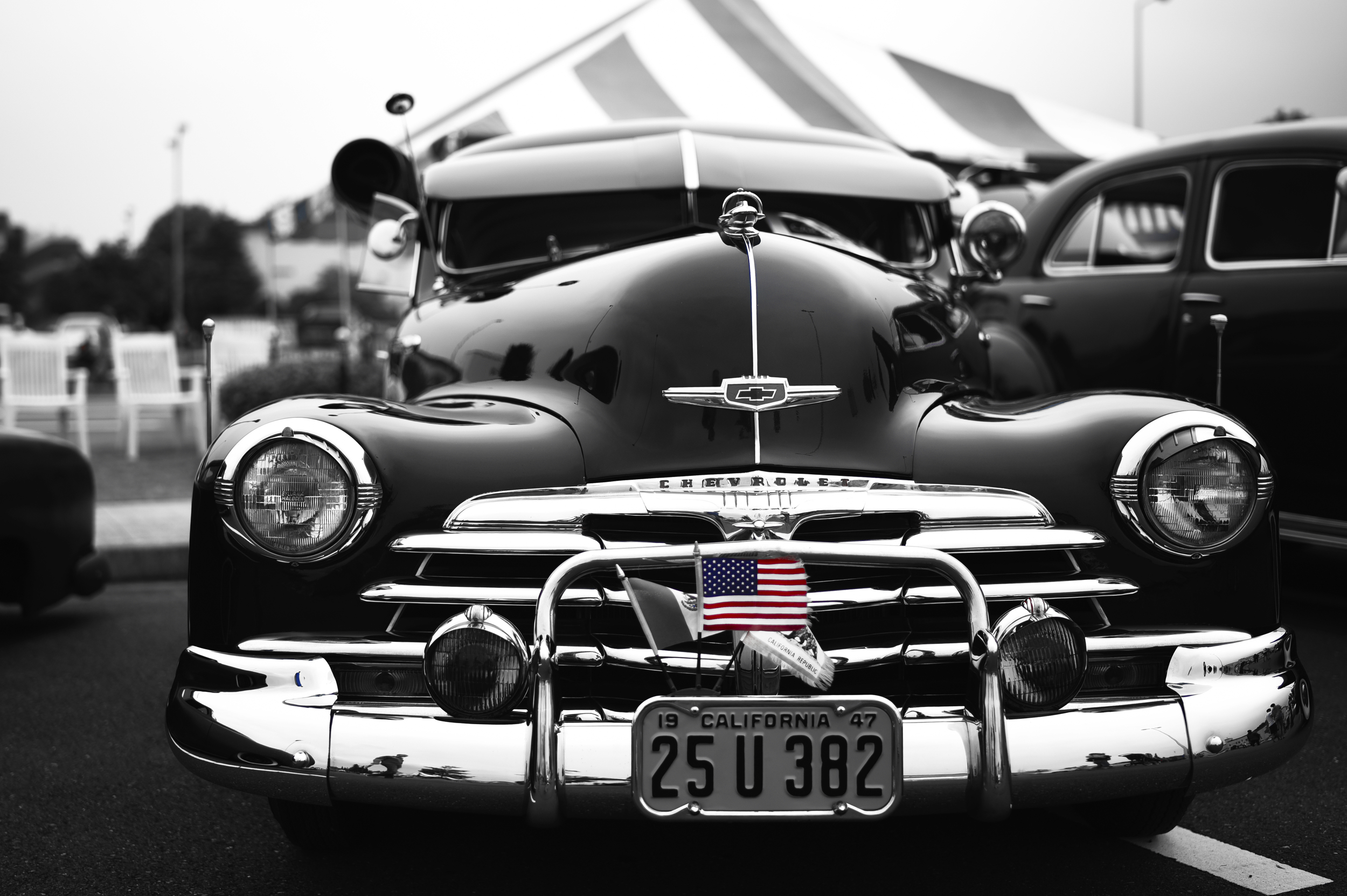 An American flag sticks out of the license plate of a Chevrolet during the car show portion of Celebrate America at Yokota Air Base, Japan, July 2, 2015. Celebrate America brings the spice of traditional Independence Day celebrations to military members stationed overseas at Yokota. (Air Force photo graphic by Senior Airman Michael Washburn/Released)