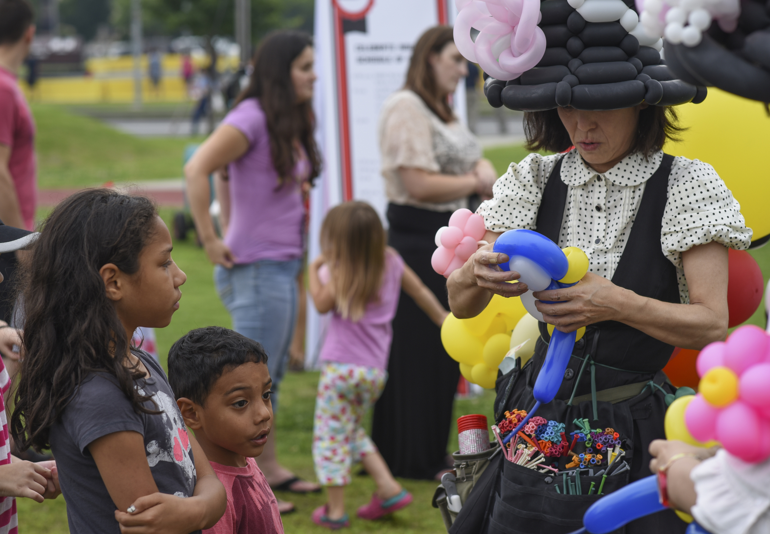 A balloon artist creates a balloon animal for children during Celebrate America at Yokota Air Base, Japan, July 2, 2015. Celebrate America is hosted every year to celebrate America's Independence Day and enhance esprit de corps. (U.S. Air Force photo by Senior Airman Michael Washburn/Released)