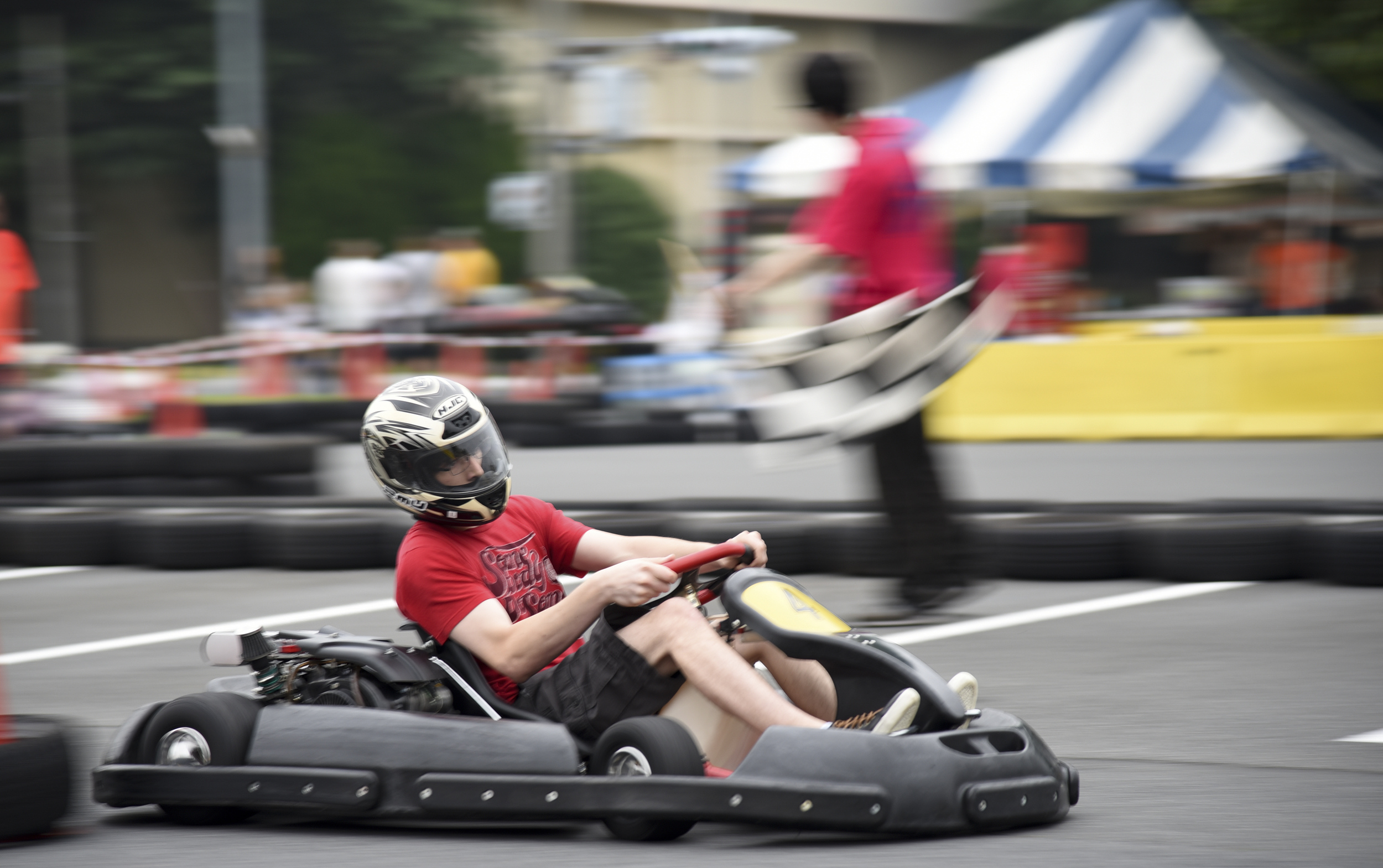 A member of Team Yokota races around the go-kart track during Celebrate America at Yokota Air Base, Japan, July 2, 2015. Some of the events during Celebrate America included live music, a petting zoo, Taiko drummers, dancers and a car show. (U.S. Air Force photo by Senior Airman Michael Washburn/Released)