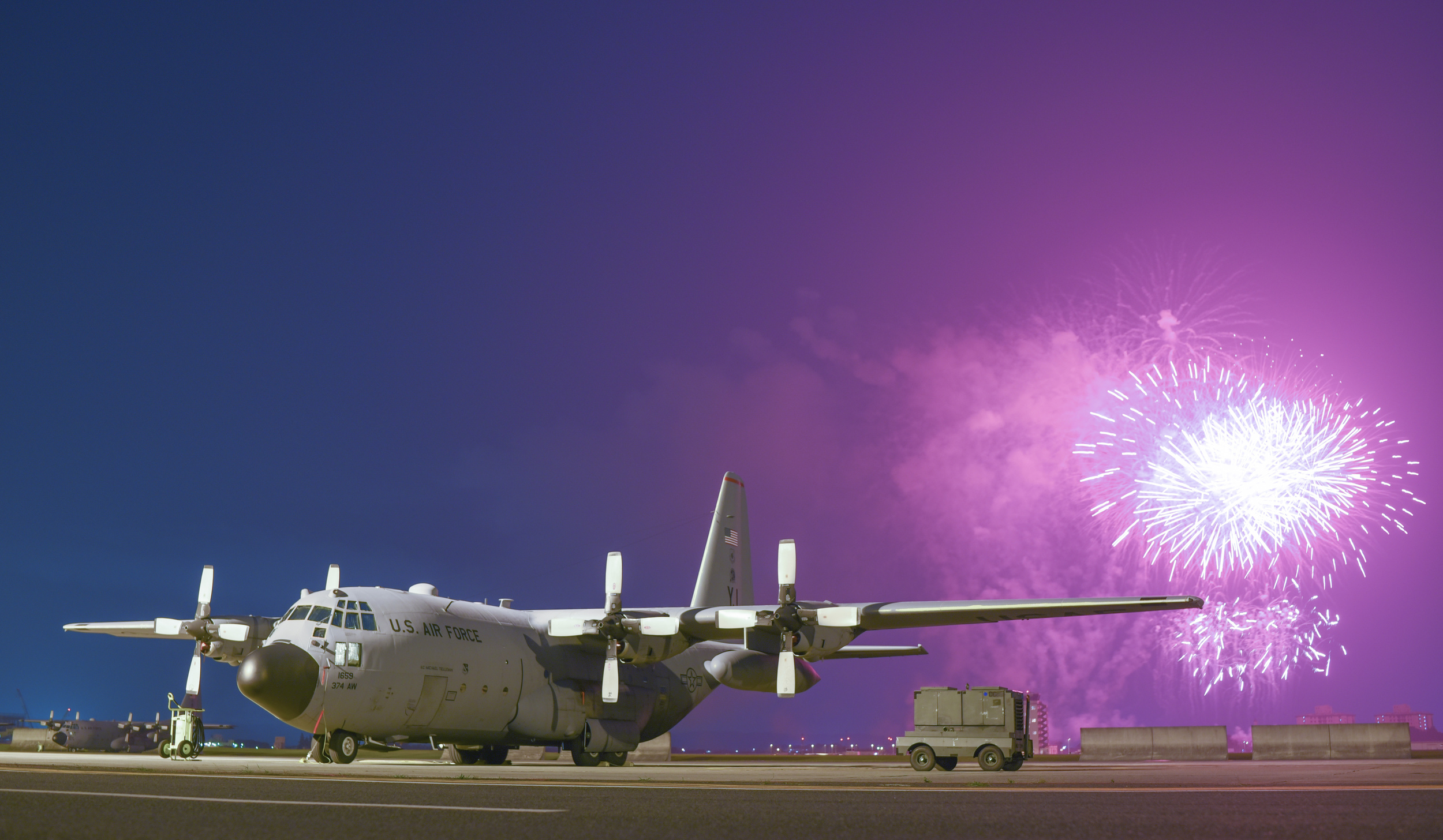 Fireworks explode behind a C-130 Hercules on the flightline during the finale of Celebrate America at Yokota Air Base, Japan, July 2, 2015. Celebrate America is hosted every year to celebrate America's Independence Day and enhance esprit de corps. (U.S. Air Force photo by Senior Airman Michael Washburn/Released)