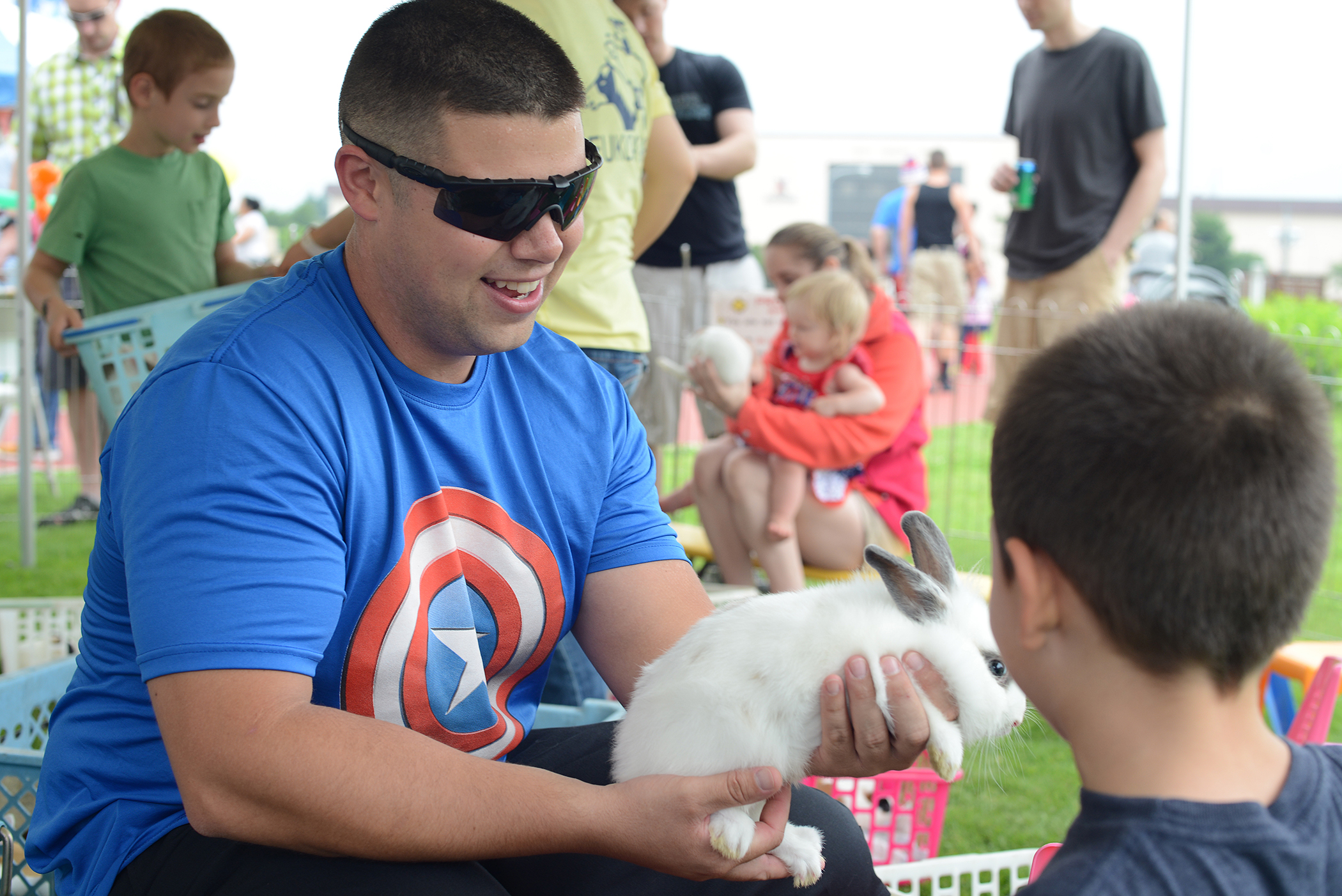 A team Yokota member holds a bunny in a petting zoo during the Celebrate America event at Yokota Air Base, Japan, July 2, 2015. The 374th Force Support Squadron hosted events throughout the day to include a 5k Fun Run, the Leaky Kon Tiki race, go-karts, carnival booths and performances from the Band of the Pacific-Hawaii 'Hana Hou!'. (U.S. Air Force photo by Airman 1st Class David C. Danford/Released)