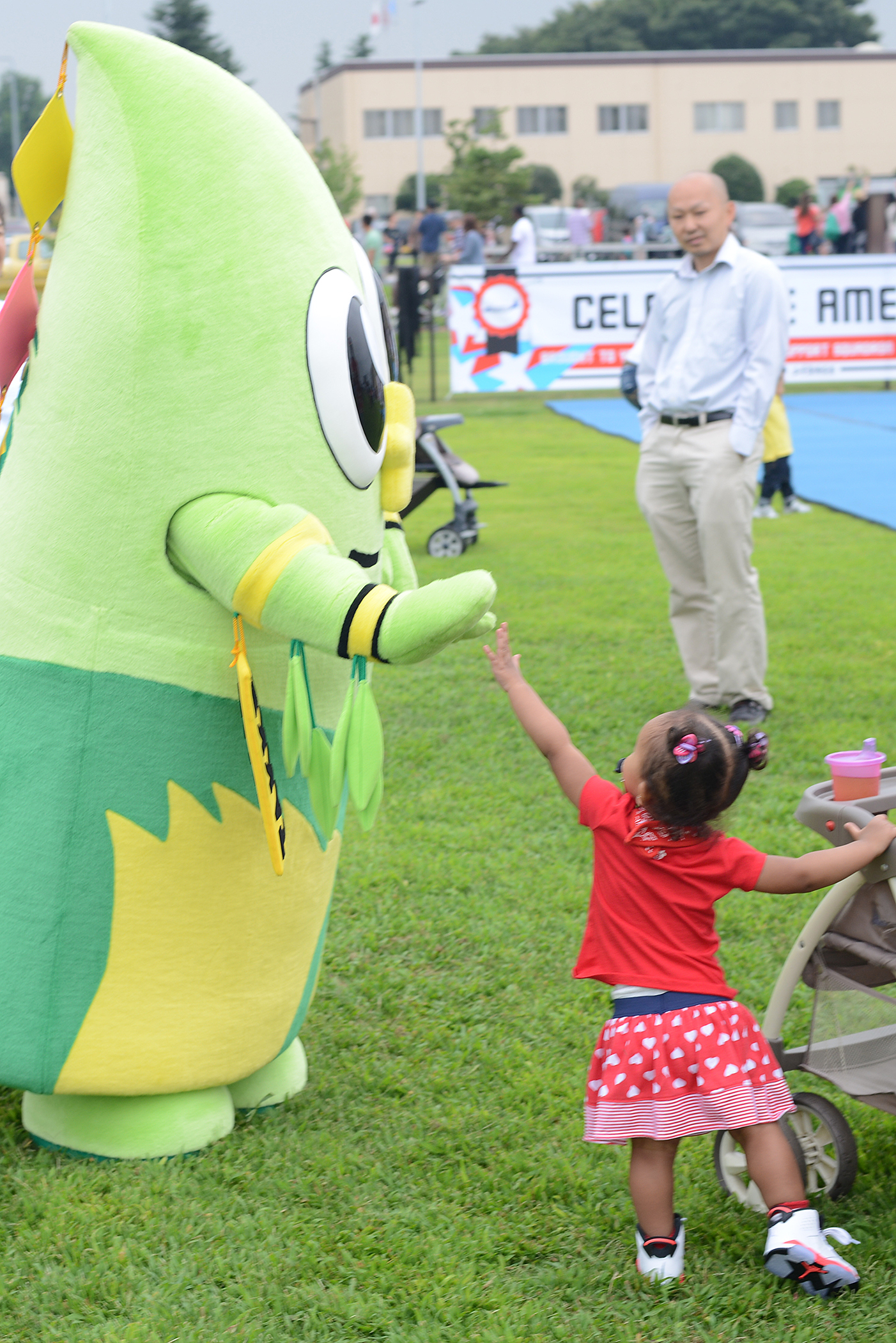 A child high-fives Takke the bamboo, mascot for Fussa city, during the Celebrate America at Yokota Air Base, Japan, July 2, 2015. Yokota borders five municipal cities, each with their own mascot. (U.S. Air Force photo by Airman 1st Class David C. Danford/Released)